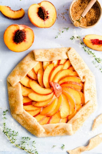 overhead shot of peach galette with sugar sprinkled crust