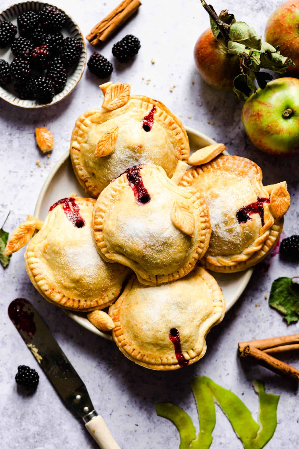 top view of a plate with 5 apple and blackberry hand pies