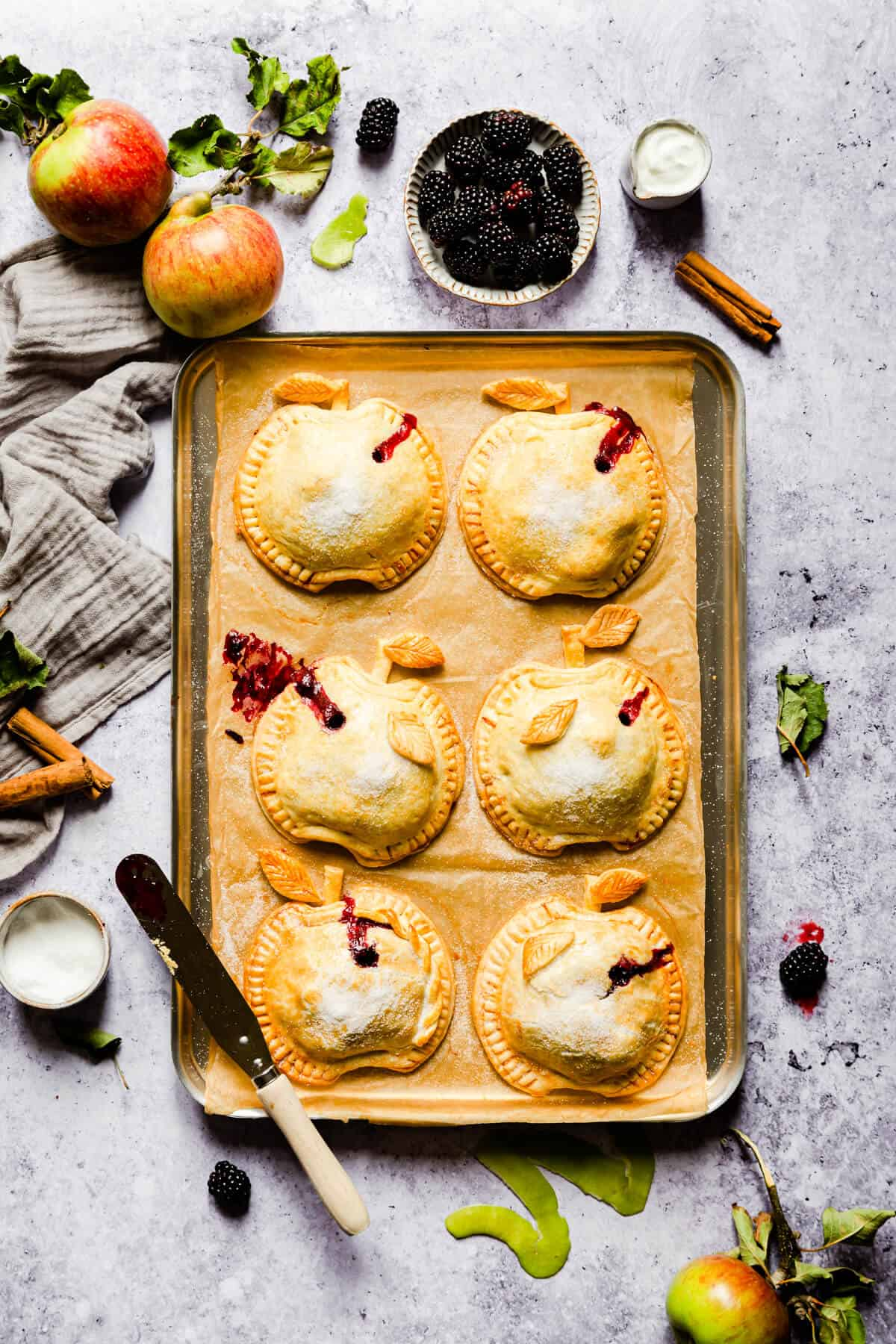 overhead shot of baked apple and blackberry hand pies on a baking tray