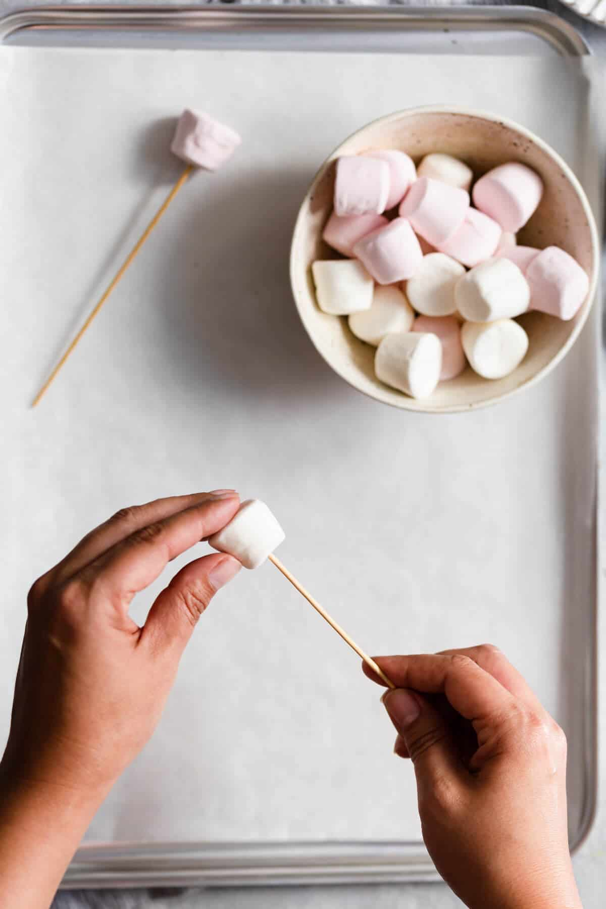 overhead shot of a person poking a bamboo skewer through a marshmallow