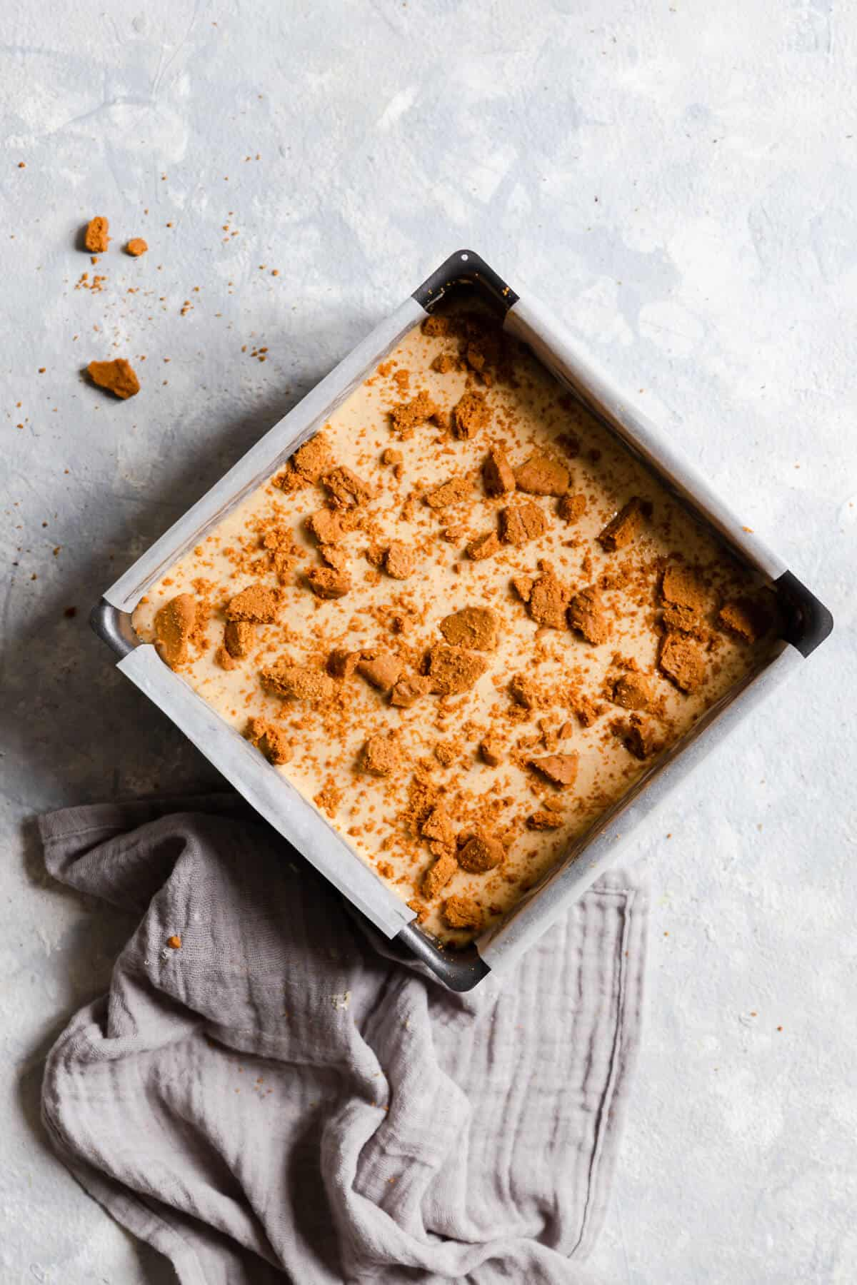 top view of cheesecake batter in a baking tin with crushed biscuits on top