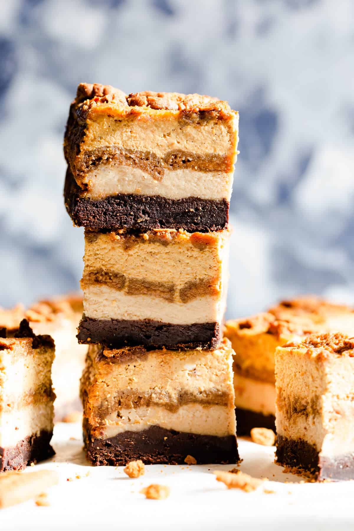 side angle shot of three slices of pumpkin biscoff cheesecake brownie bars stacked on top of each other