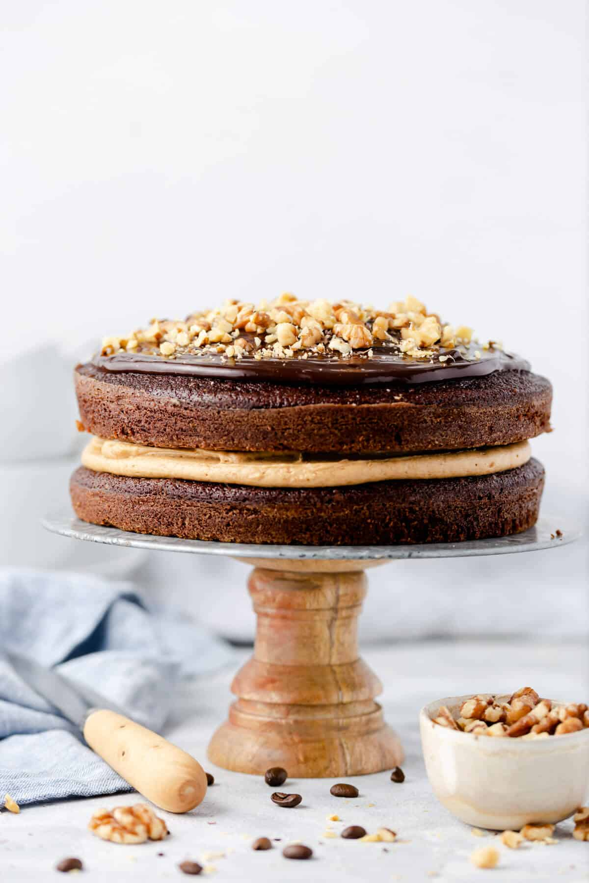 straight ahead shot of a coffee cake on a cake stand topped with ganache and chopped walnuts