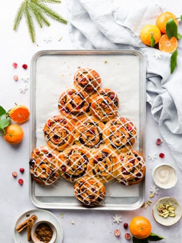 overhead shot of orange and cranberry Chelsea buns shaped into a Christmas tree with sugar glaze