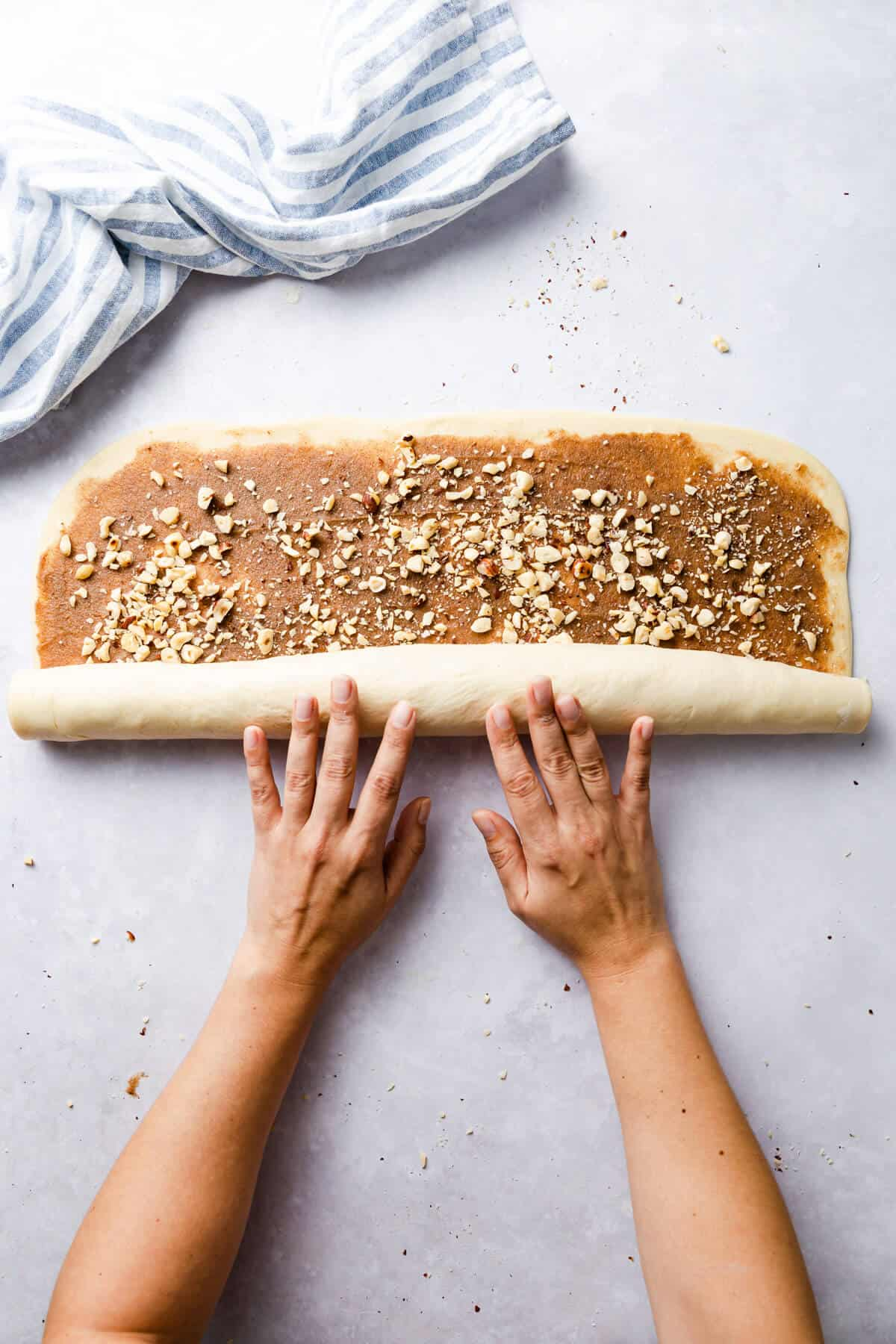 top view of dough for twisted cinnamon and hazelnut bread being rolled into a large log