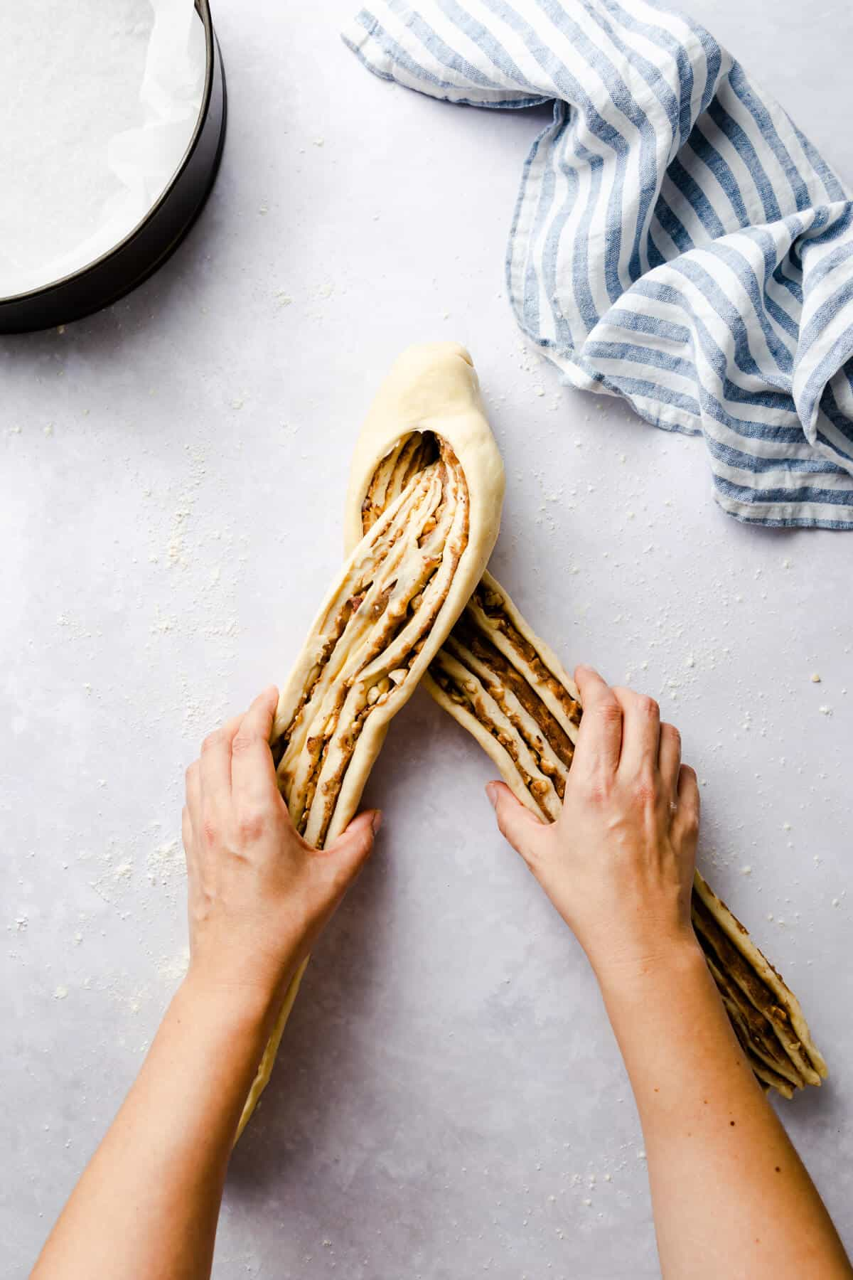 top view of a person shaping a sliced log of dough into a cross pattern