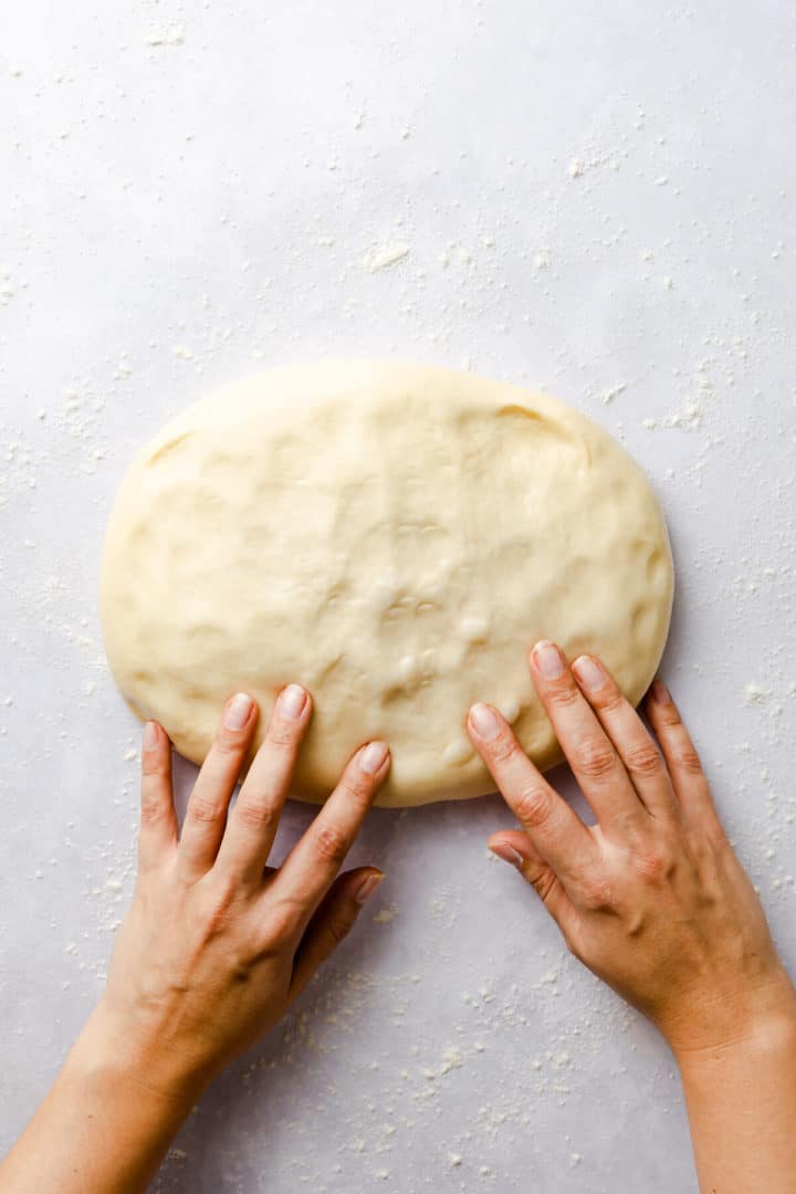 top view of person knocking the air out of soft dough