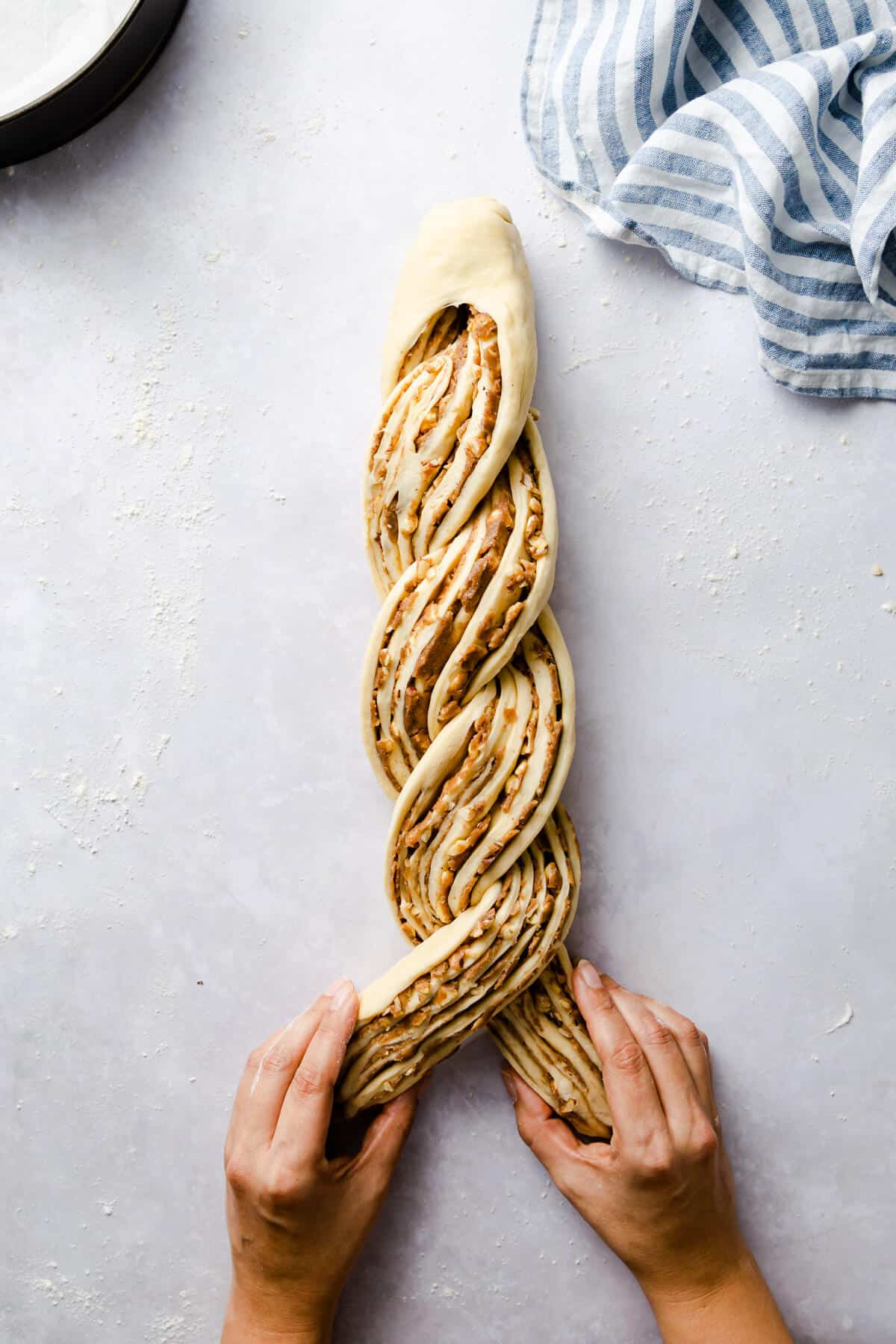 top view of a dough being twisted for cinnamon and hazelnut bread