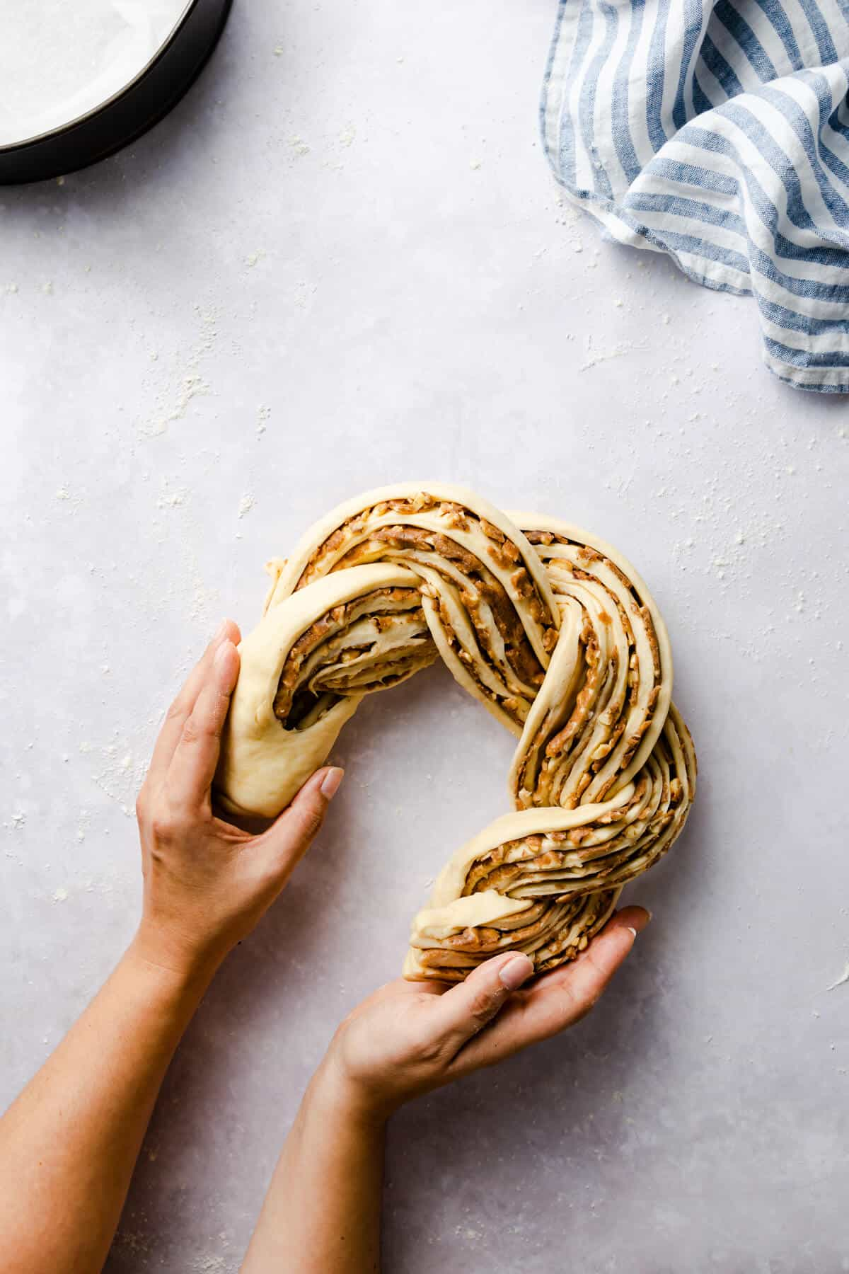 overhead shot of a person shaping twisted cinnamon bread into a circle