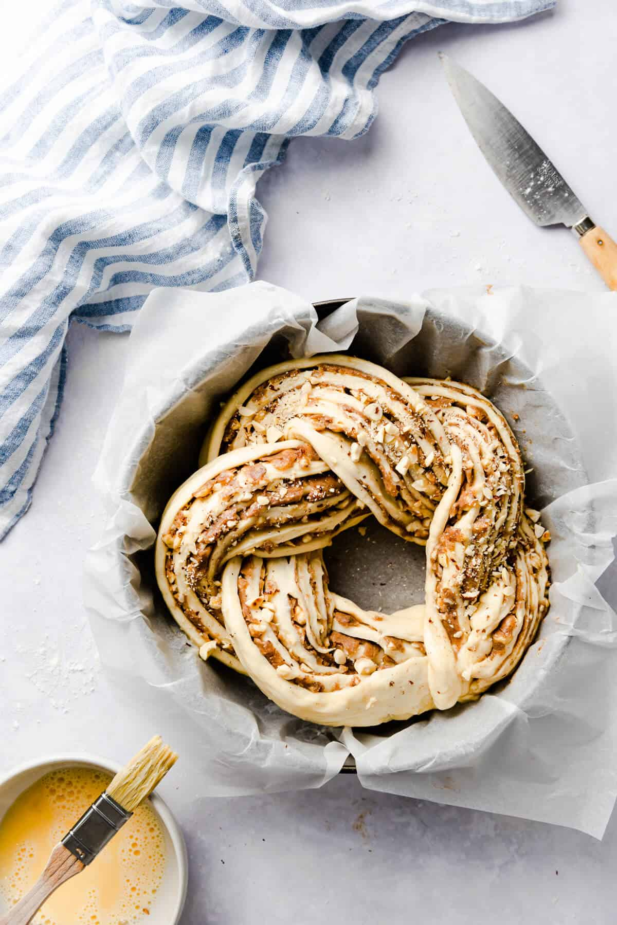 top view of twisted cinnamon and hazelnut bread in a baking tin with baking paper