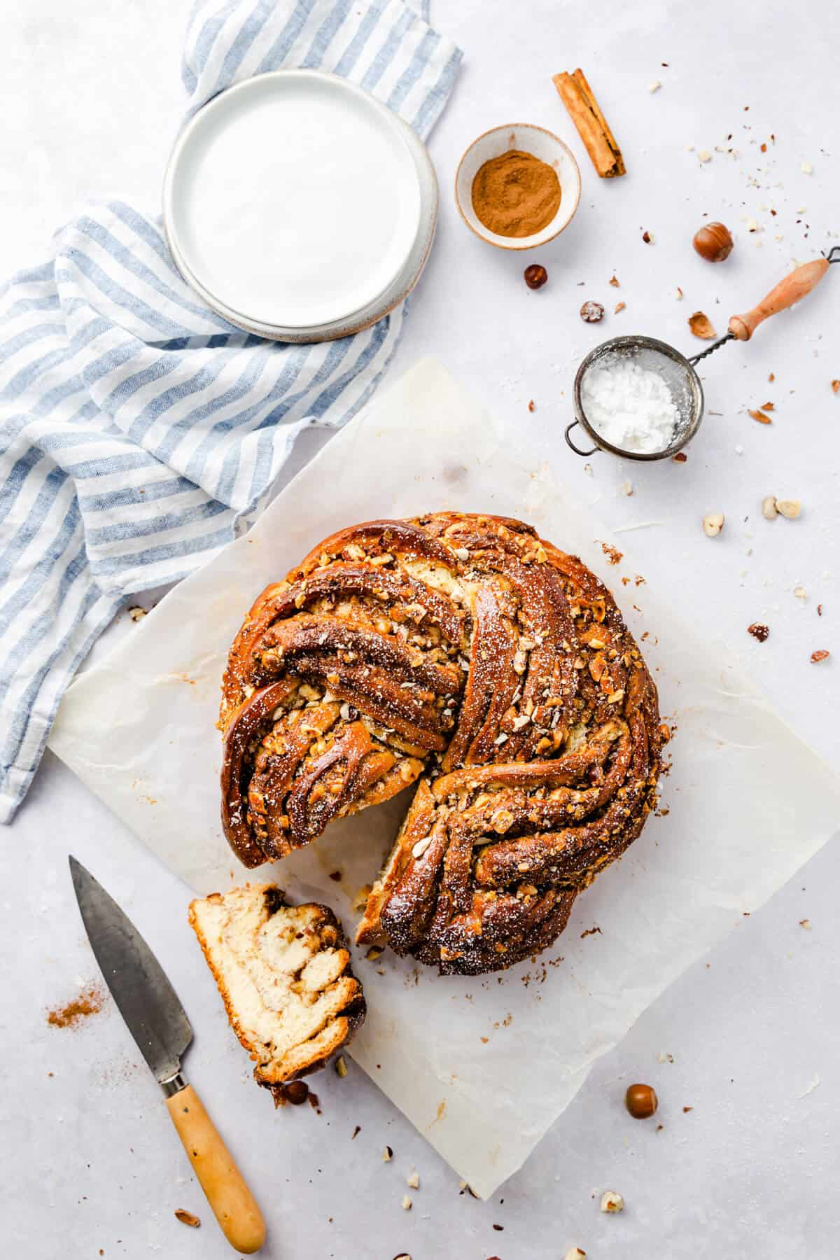 overhead shot of a twisted cinnamon and hazelnut bread with a slice cut out on side