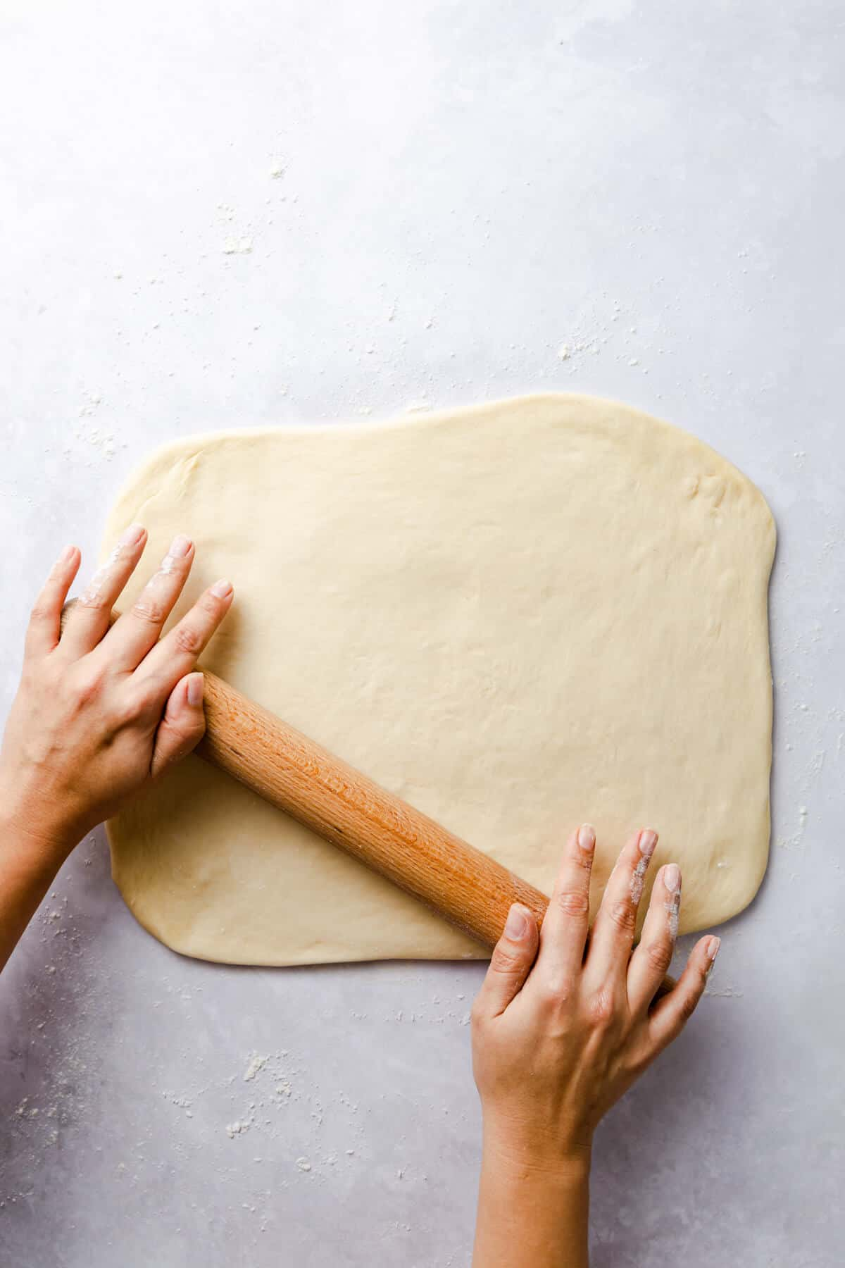 top view of a person rolling the dough into rectangle with rolling pin