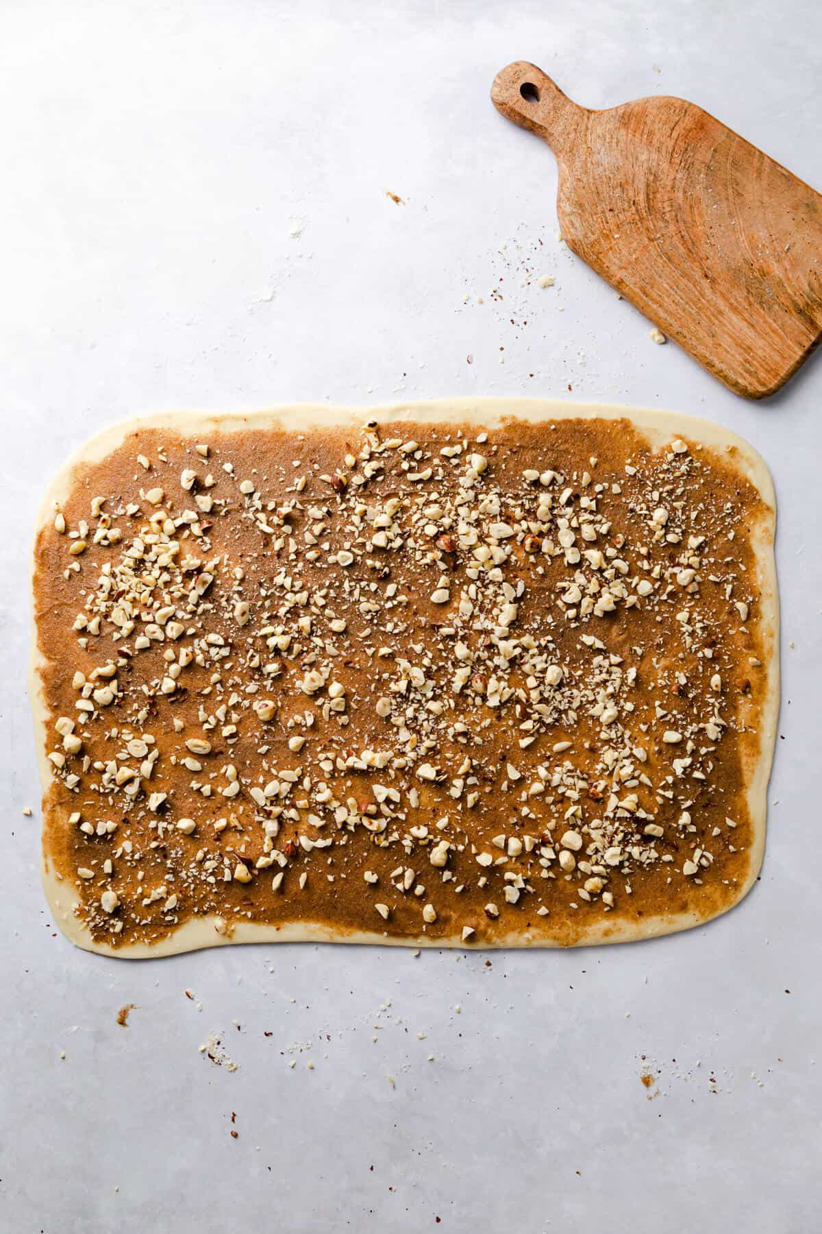 top view of dough rectangle covered in cinnamon butter and chopped hazelnuts
