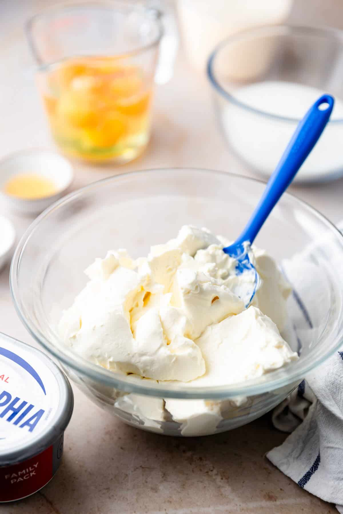 a side shot of a glass bowl with cream cheese inside