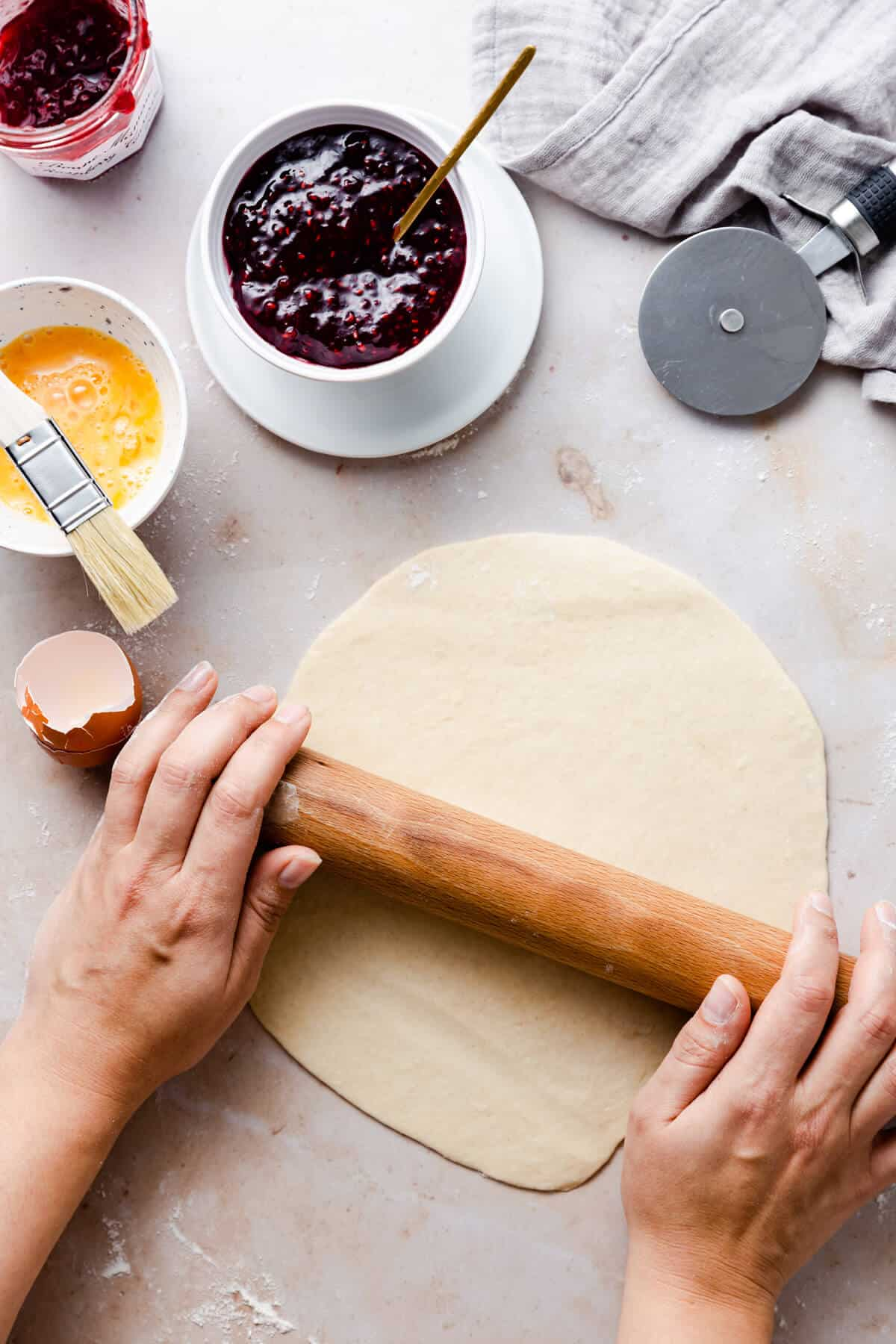 top view of a person rolling the dough into circle with wooden rolling pin