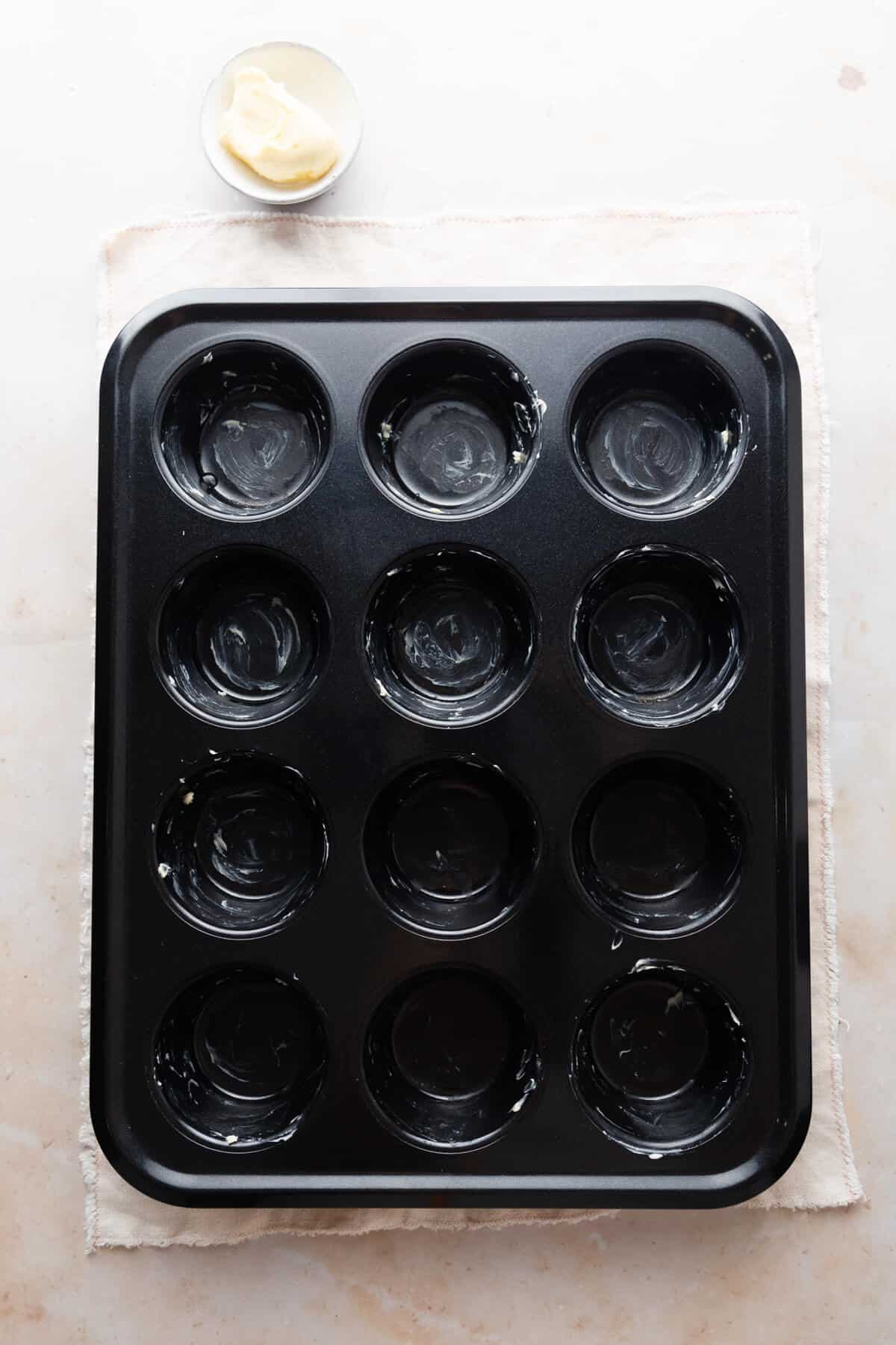 overhead view of a 12- hole muffin tin greased with butter