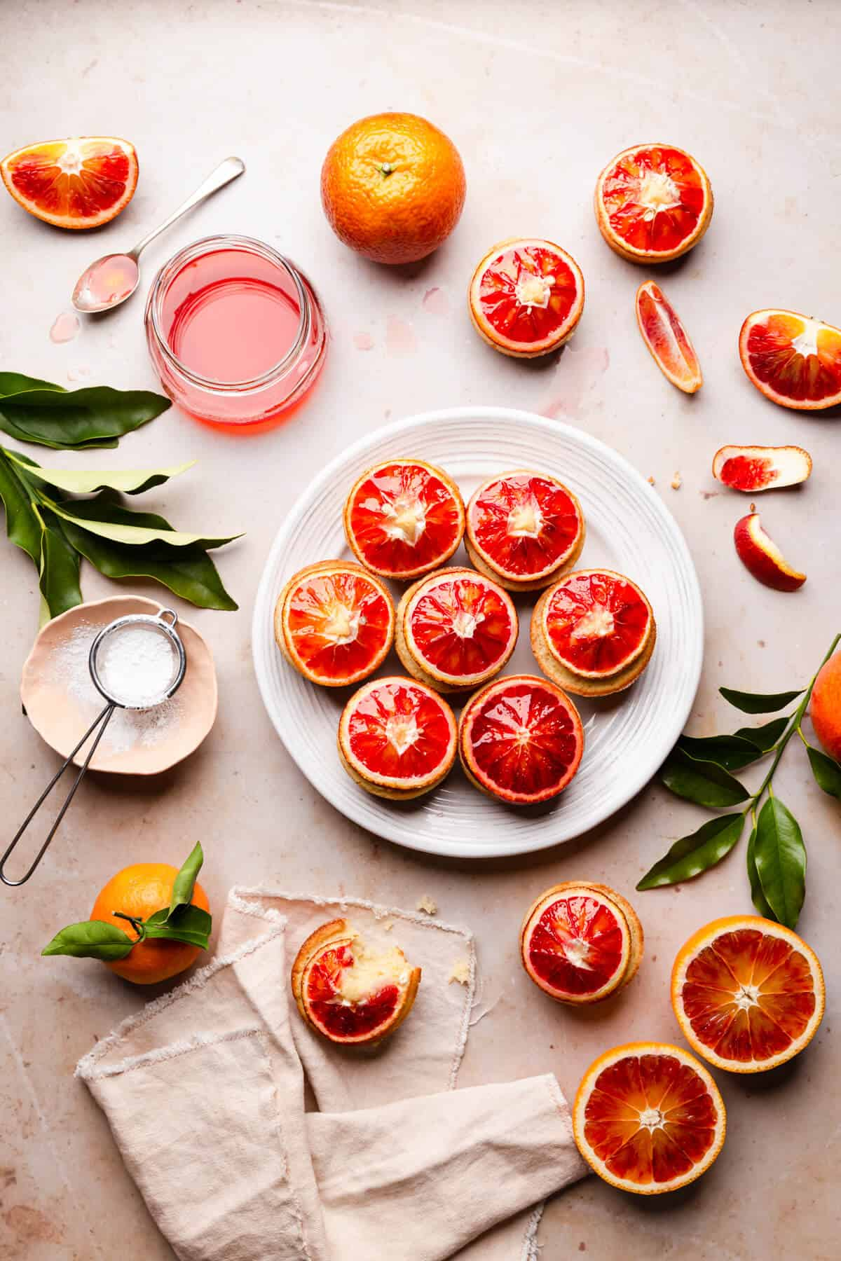 overhead view of blood orange and semolina cakes on a large white plate and some blood orange slices around it