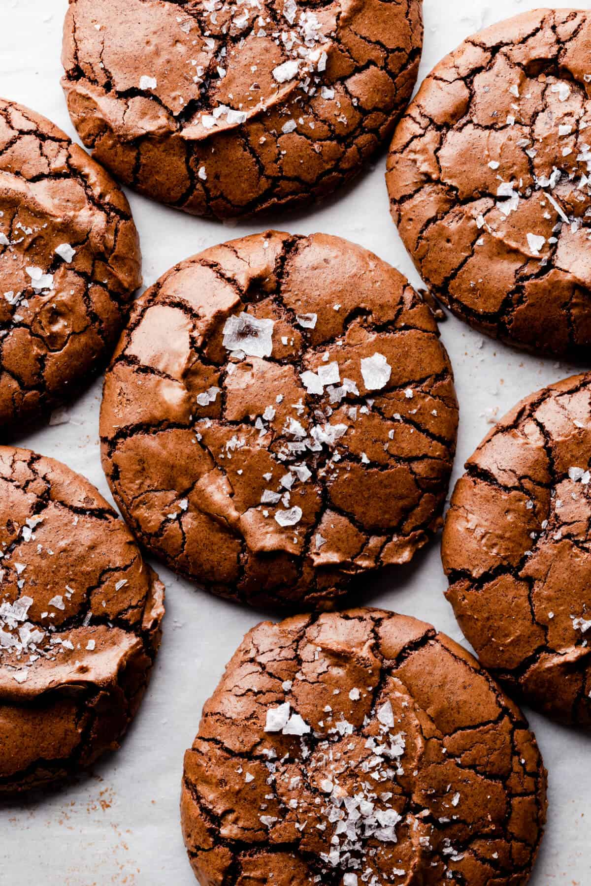 overhead super close up at brownie cookies with crinkled tops and flaked sea salt