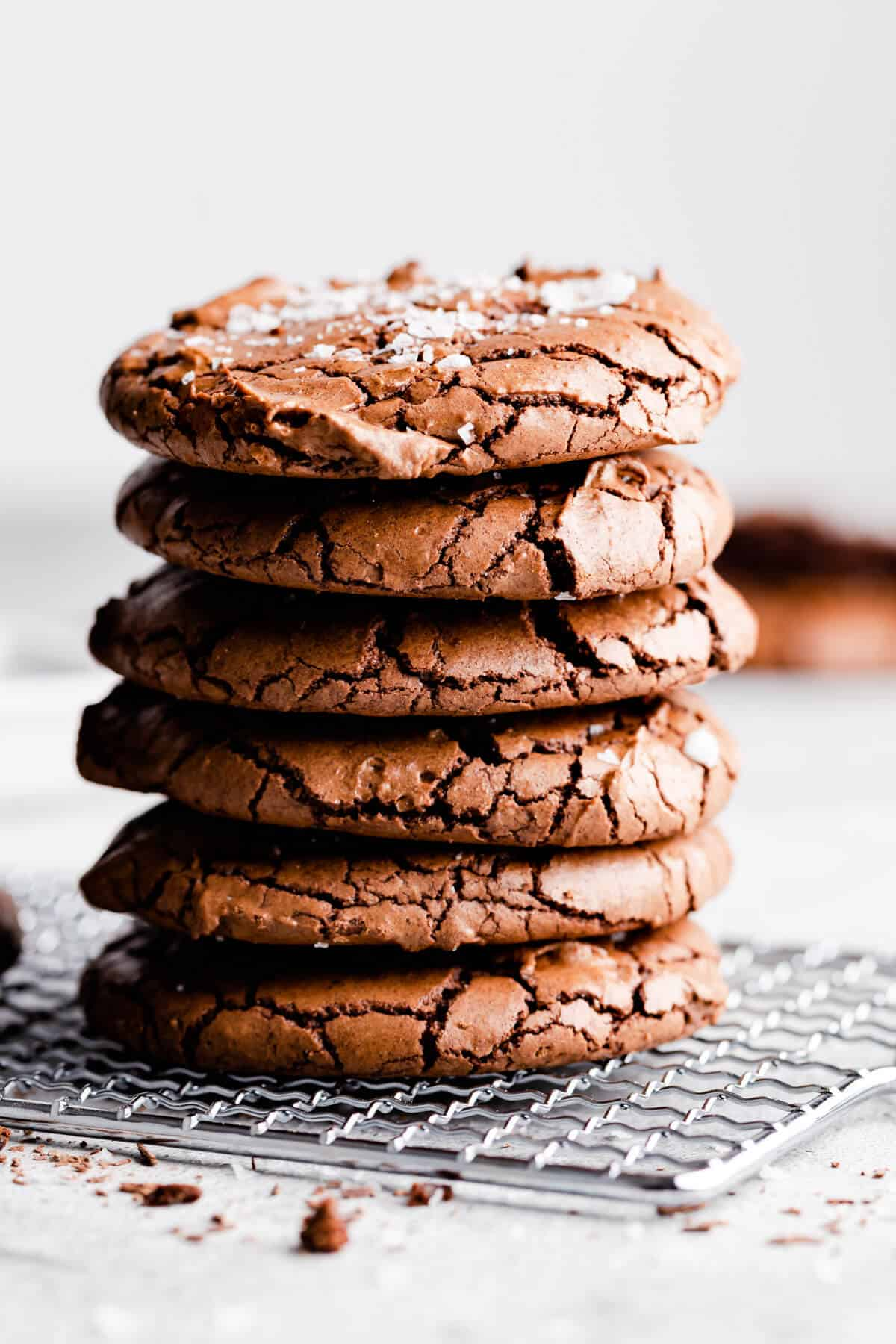 straight ahead angle super close up at a stack of 6 chocolate brownie cookies with flaked sea salt on top