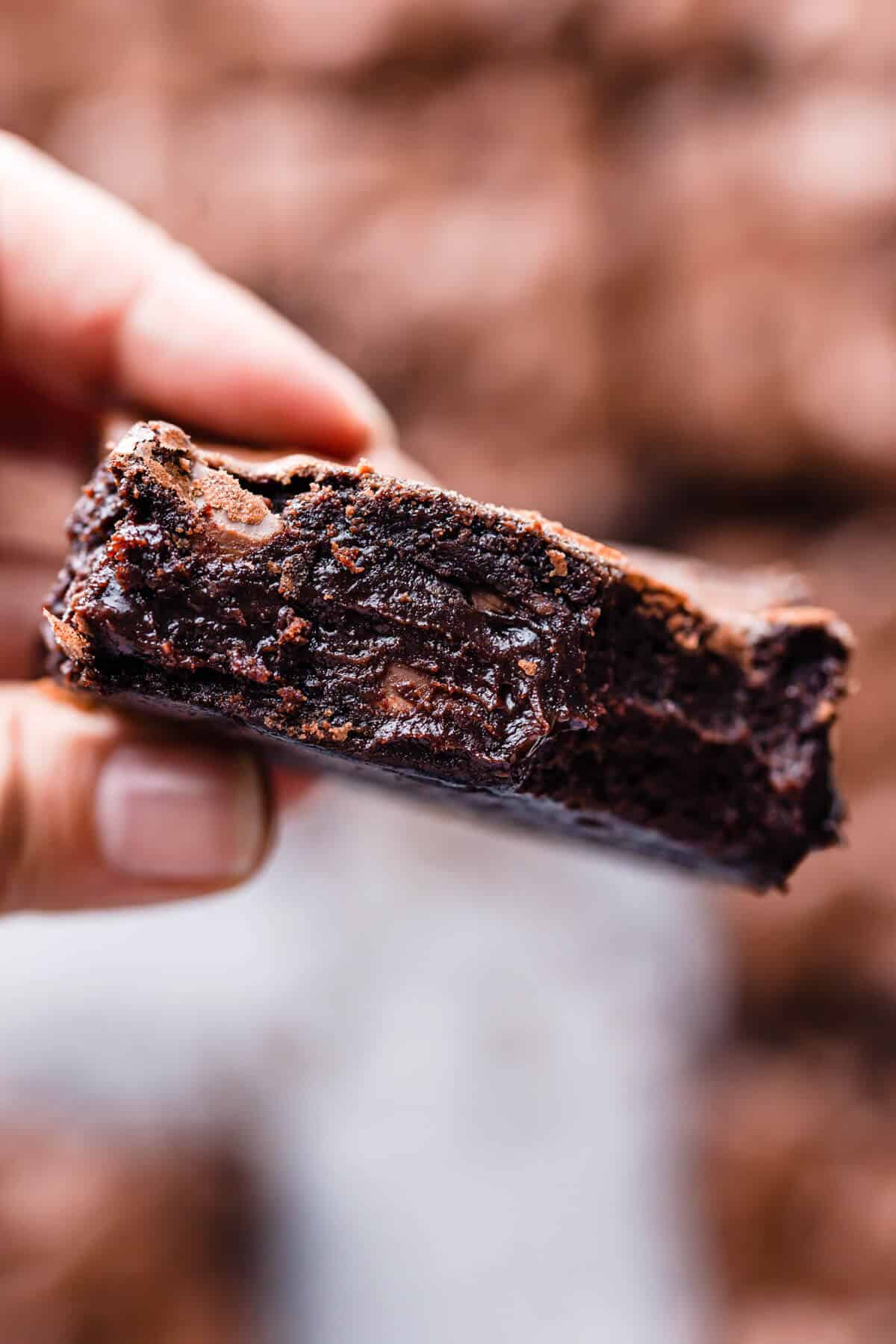 super close up of a person holding a slice of brownie showing it's gooey texture