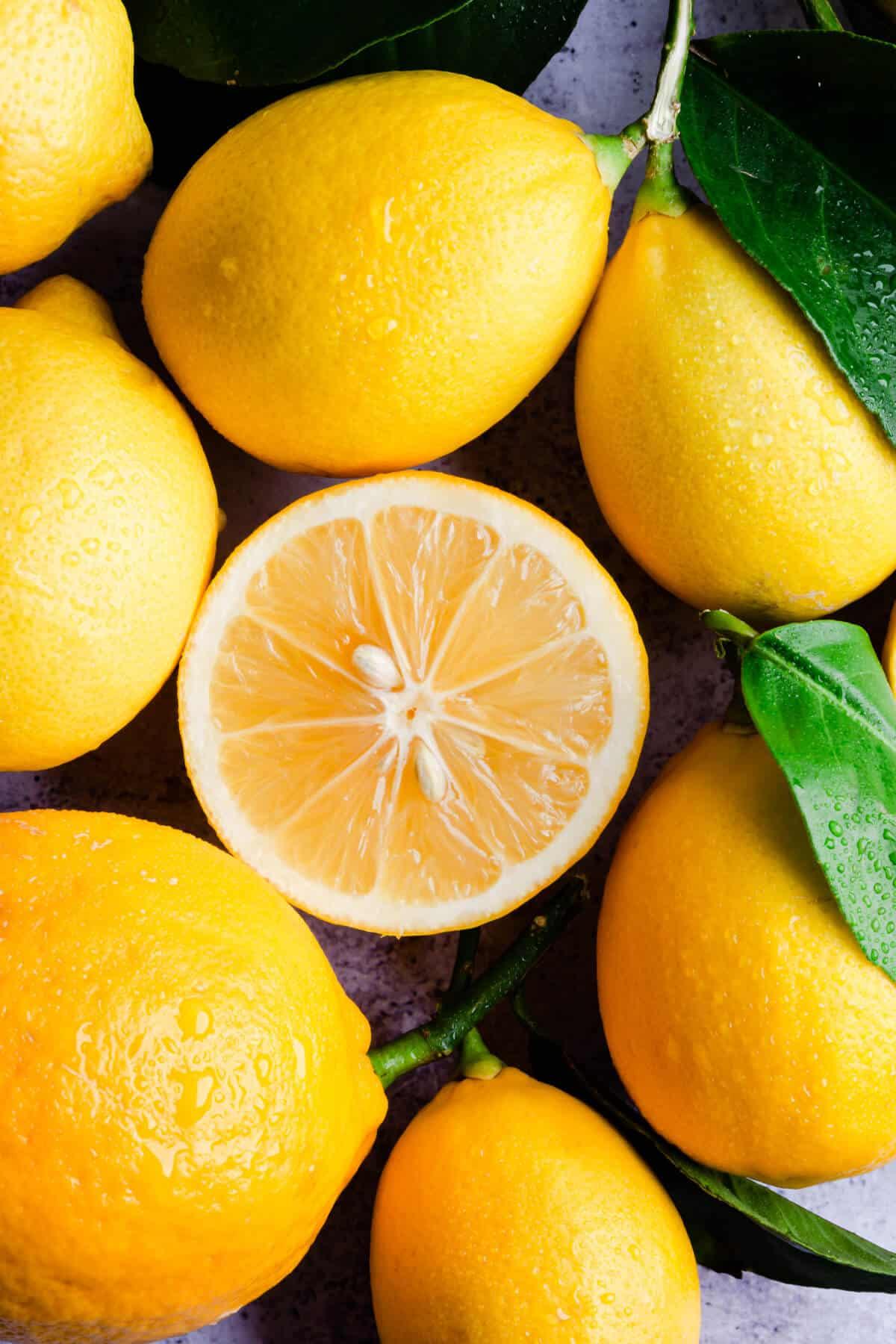 top view super close up at fresh lemon half surrounded by whole lemons