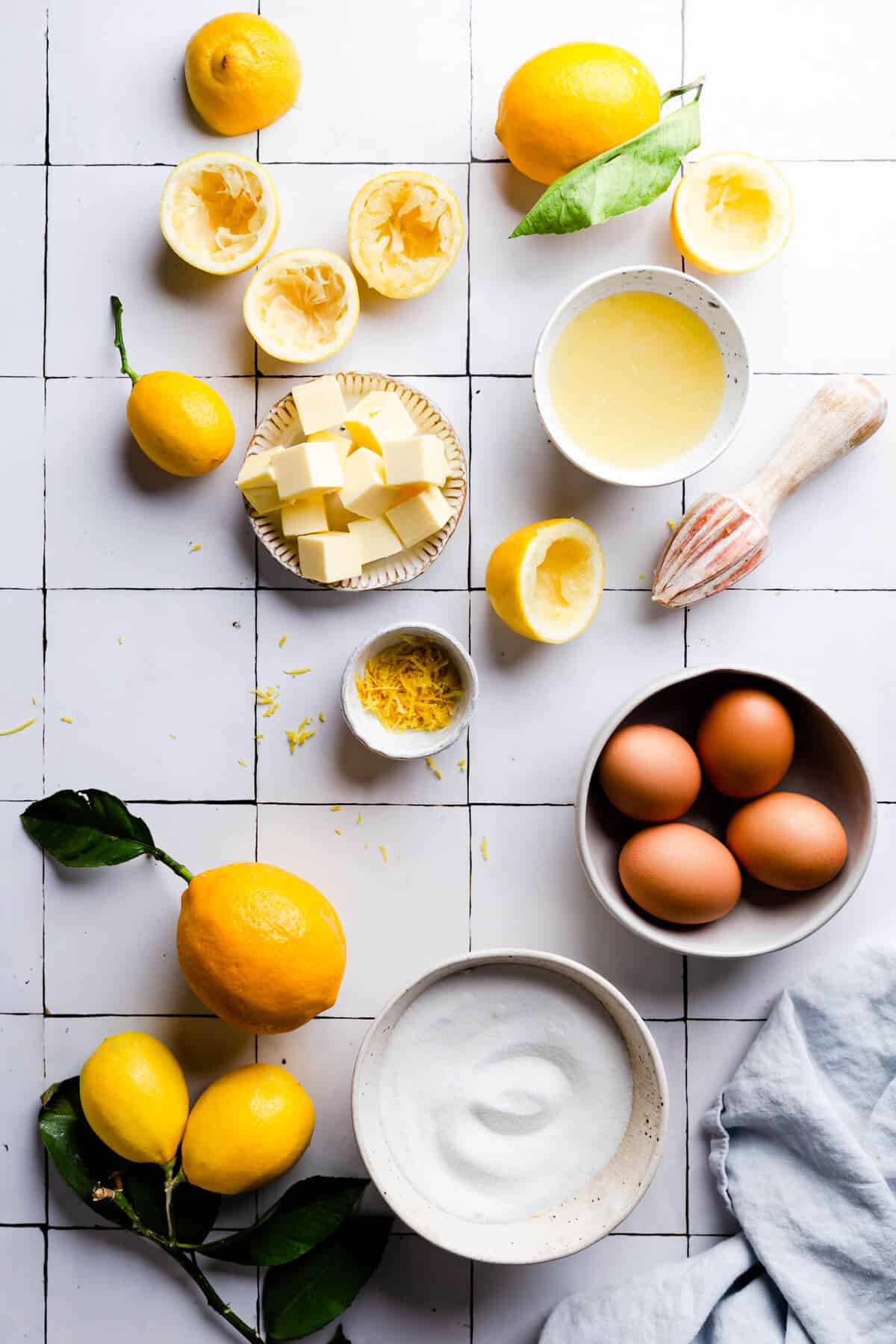 overhead shot of the ingredients for homemade lemon curd on a white tile surface