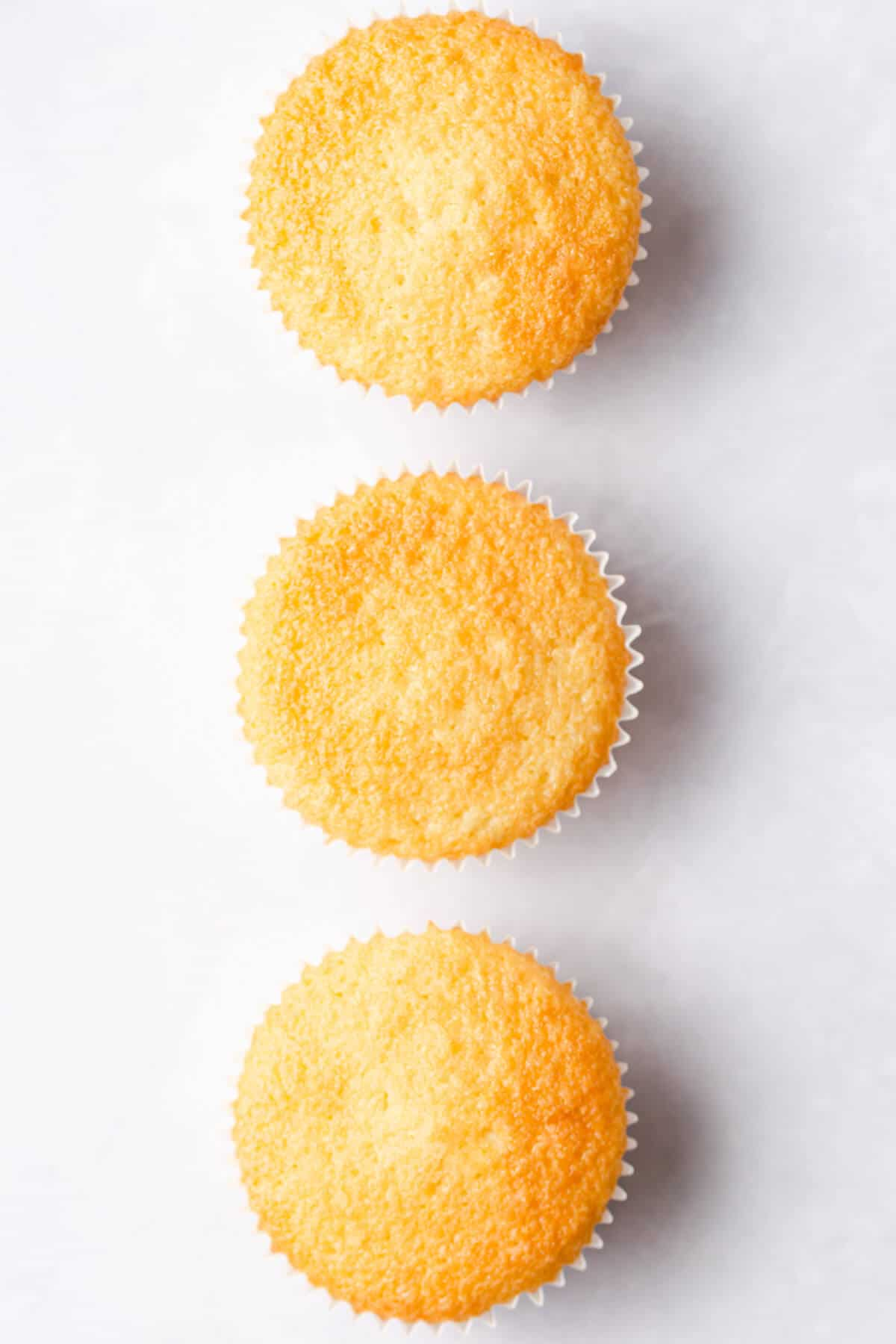 overhead view of 3 vanilla cupcakes with smooth and even tops