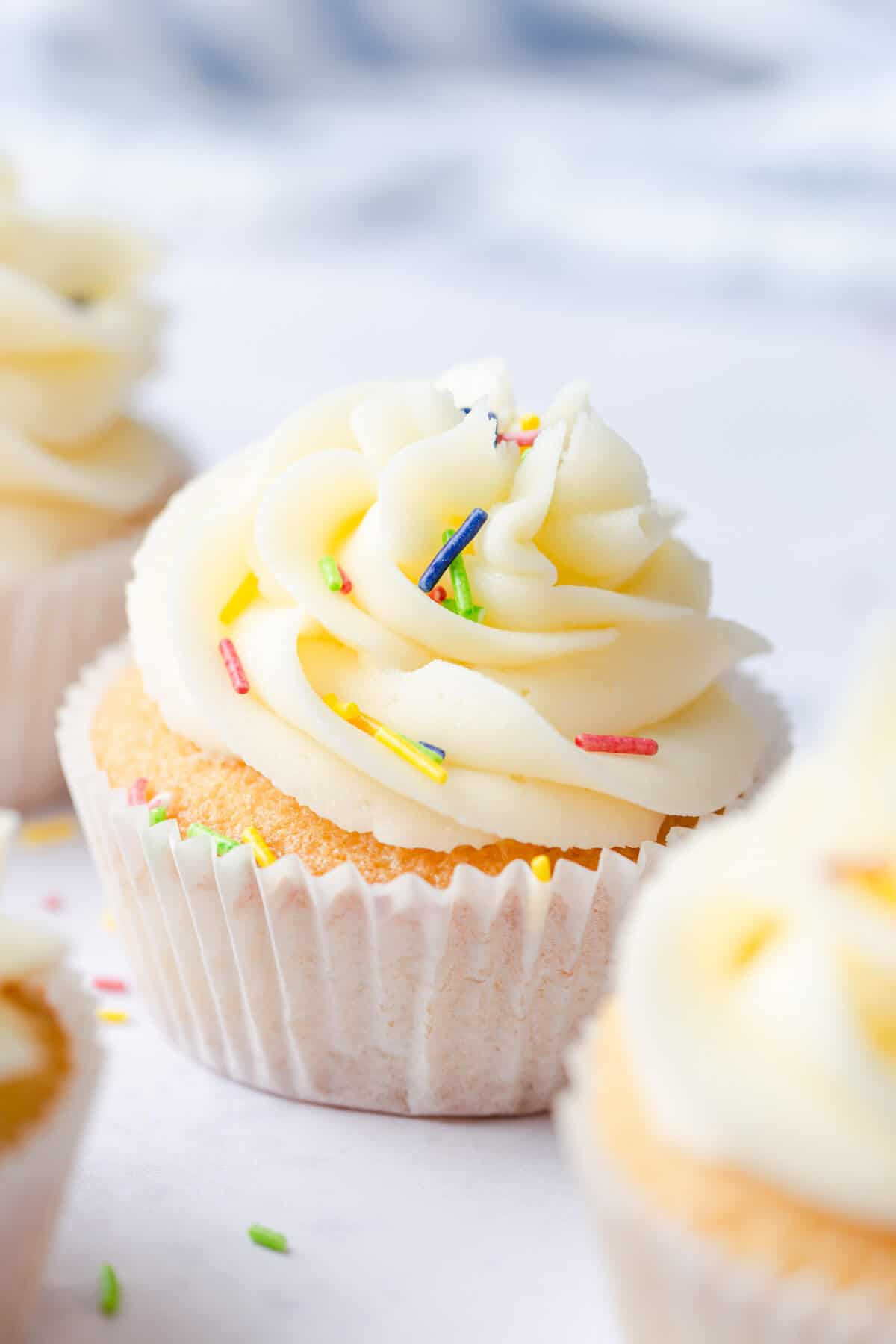 side close up of a one bowl vanilla cupcake with buttercream and coloured sprinkles on top