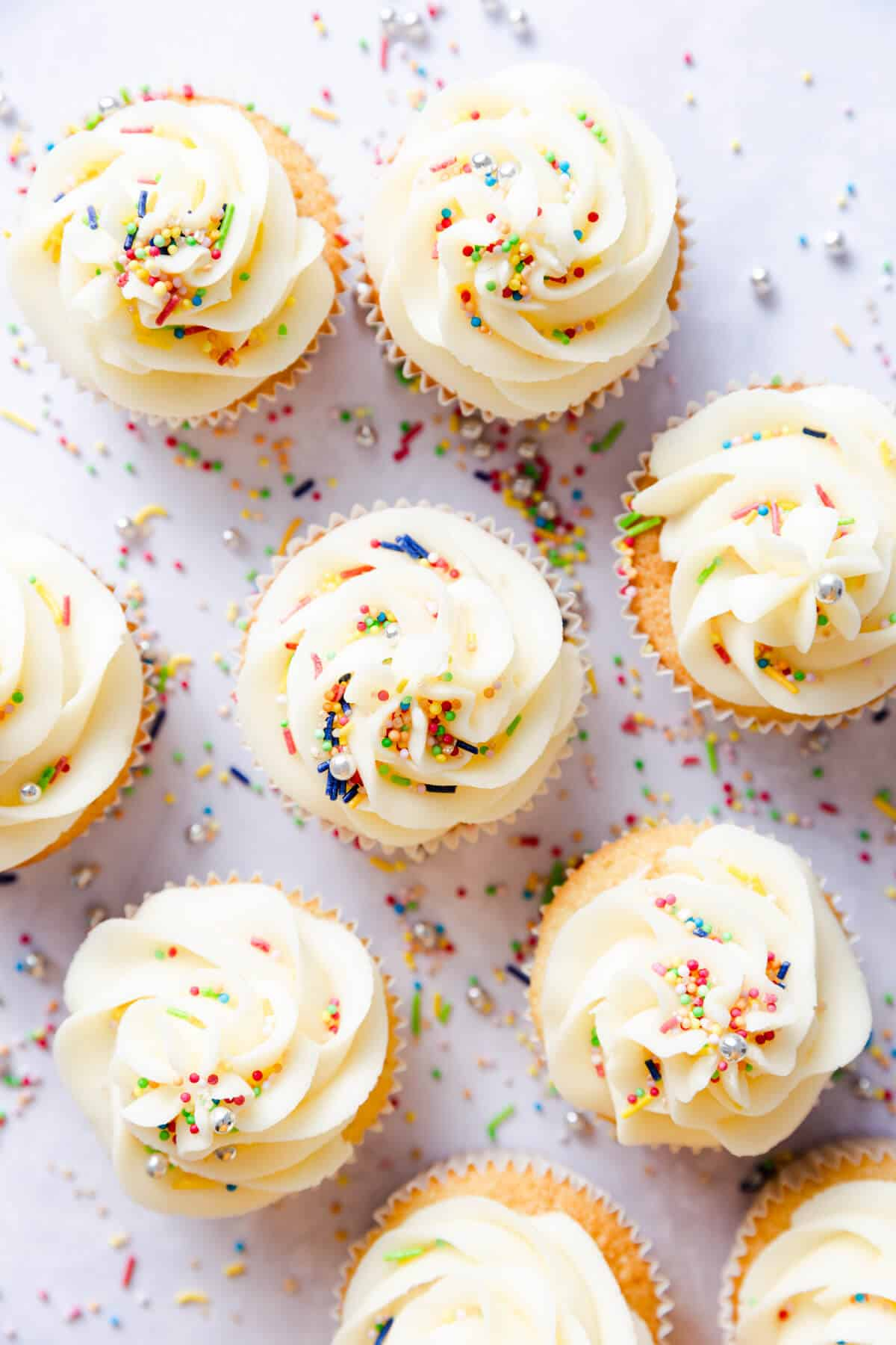 overhead shot of vanilla cupcakes with buttercream and colourful sprinkles