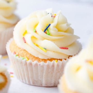 side super close up at vanilla cupcake topped with buttercream and sprinkles