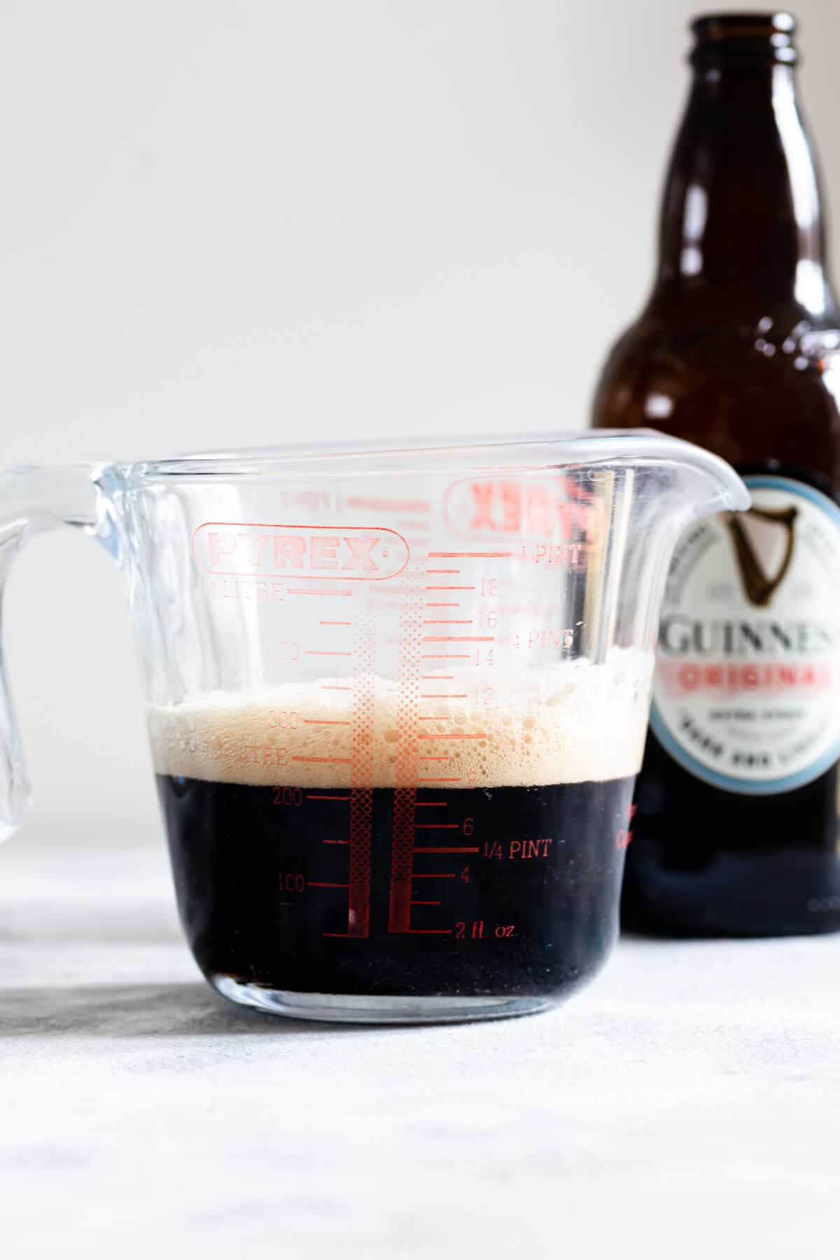 side close up photo of a glass jug with Guinness inside
