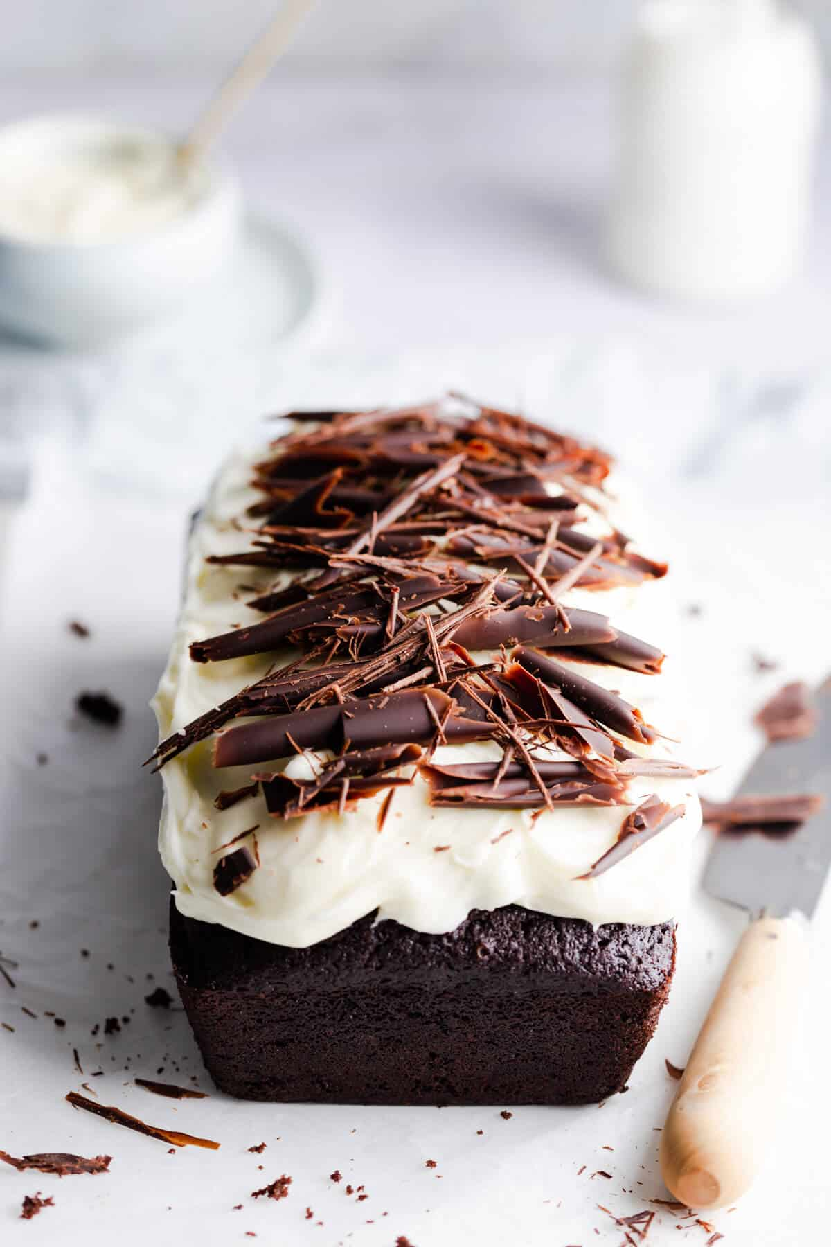 45 degree angle photo of chocolate loaf cake with frosting and chocolate curls