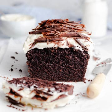 side close up photo of Guinness chocolate loaf cake topped with frosting and chocolate curls