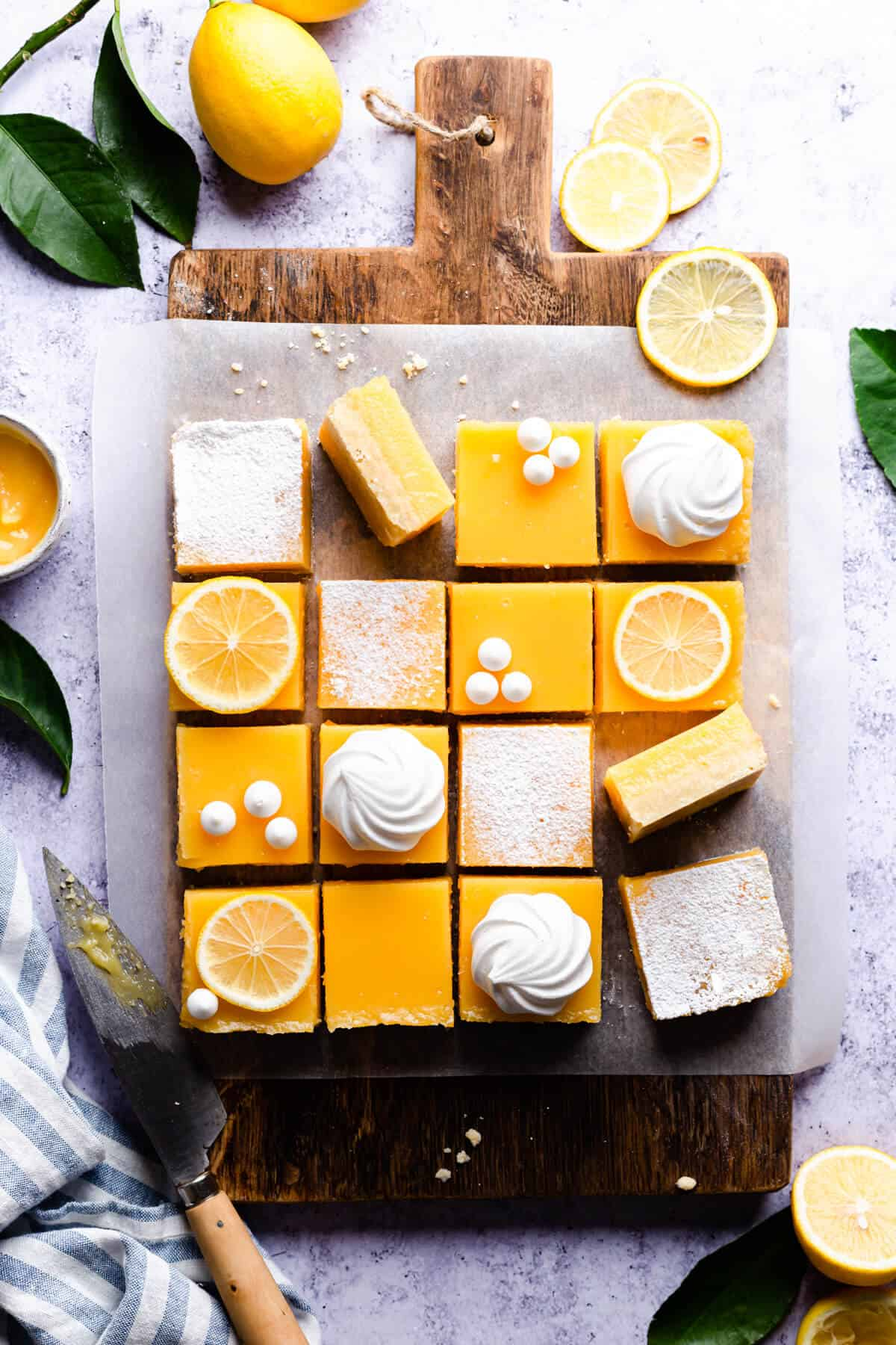 overhead shot of lemon bars cut into squares and topped with lemon slices and meringues
