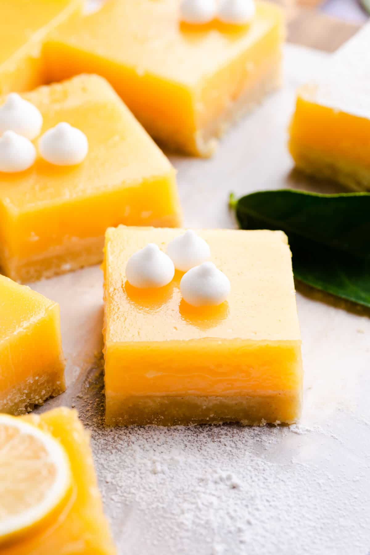 45 degree angle close up at a square lemon curd slice with mini meringues on top