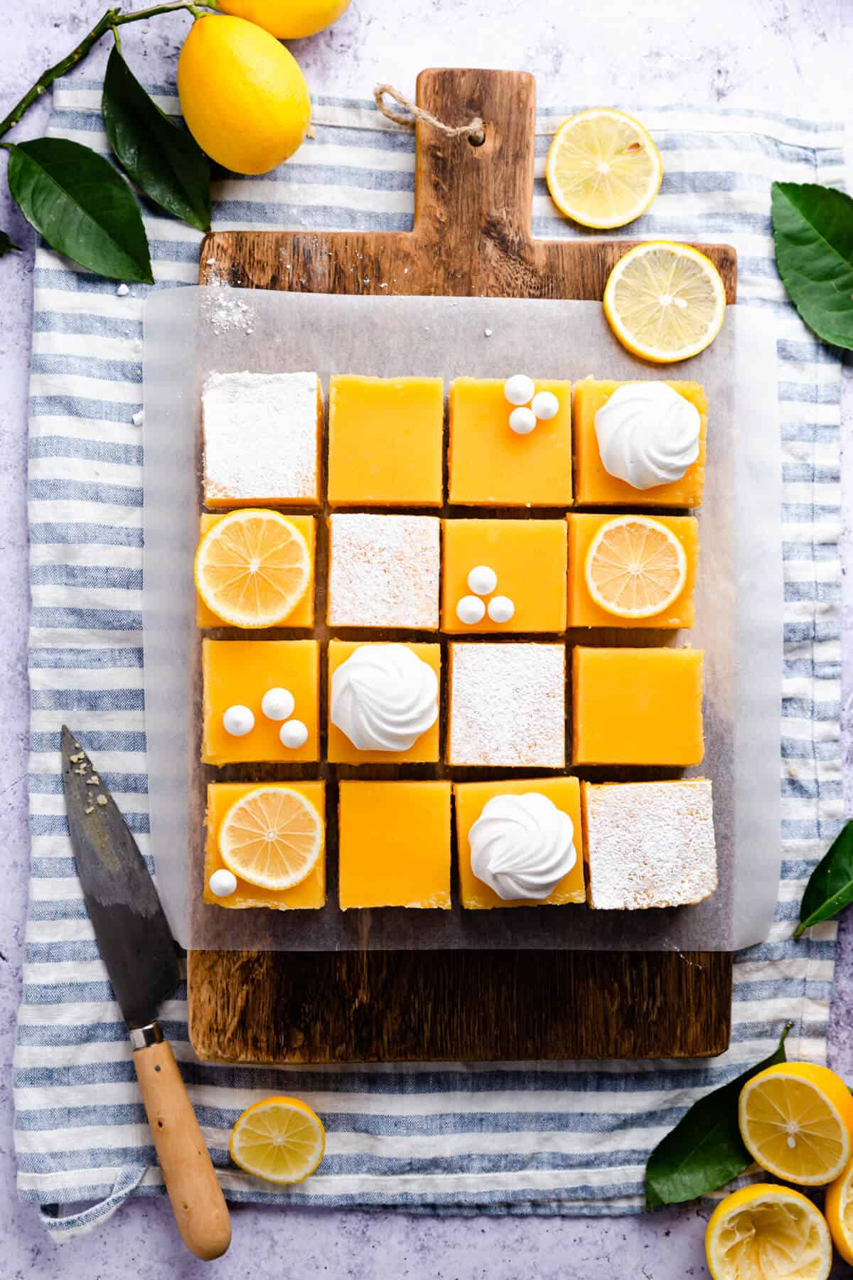 overhead photo of 16 lemon curd slices on a wooden chopping board