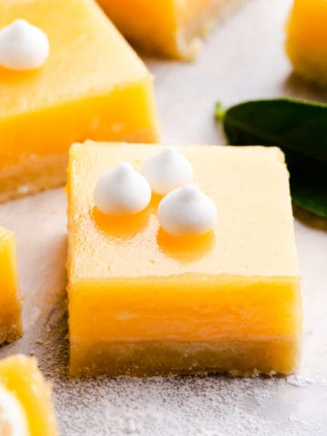 side angle super close up at a square slice of lemon curd bars topped with mini-meringue