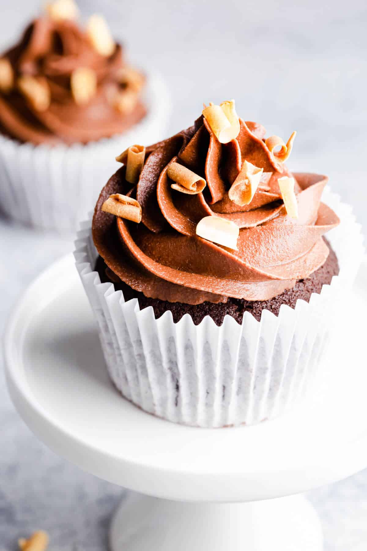 a side angle photo of a single chocolate cupcake on a small white cupcake stand