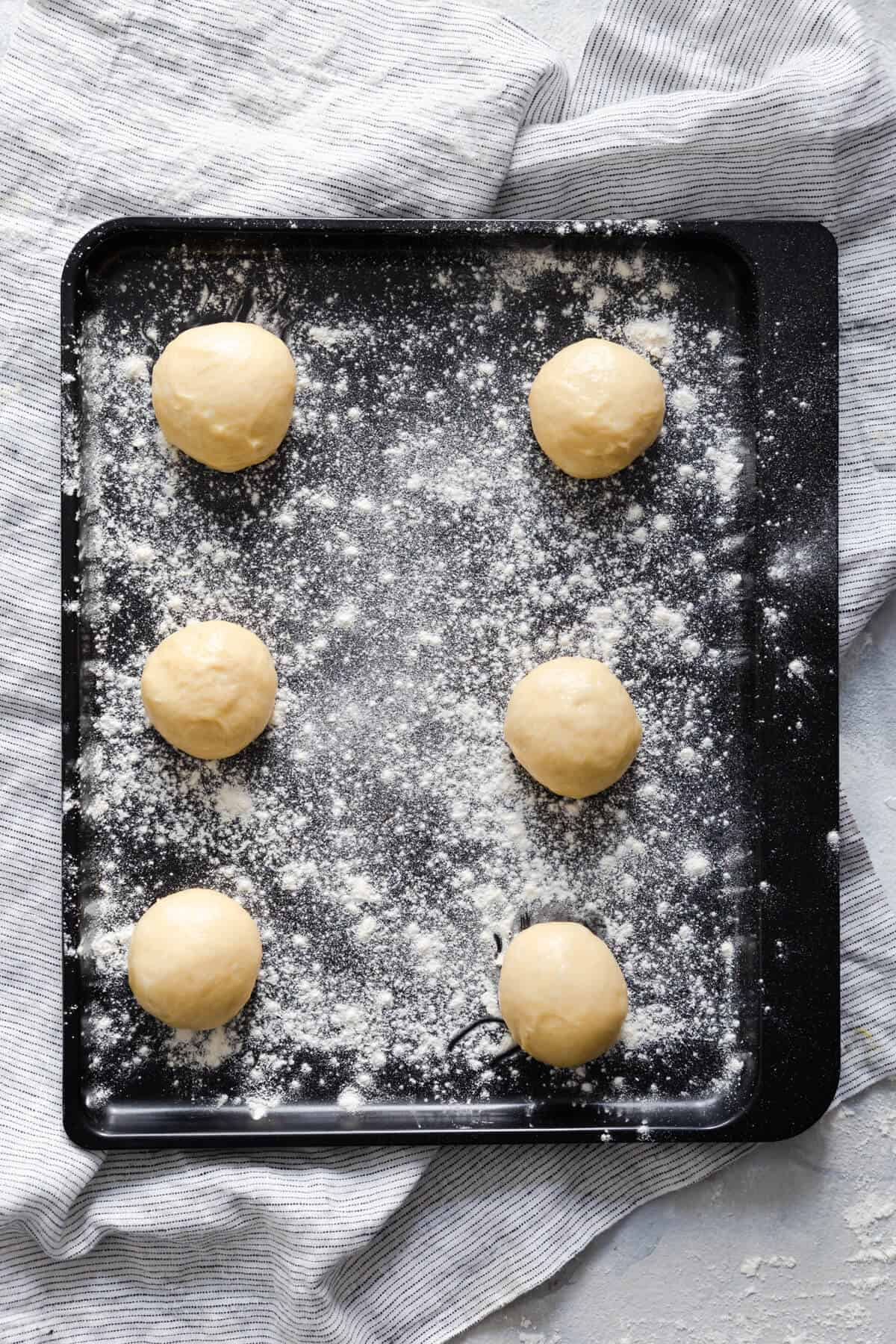 top view of 6 dough balls on a floured baking tray