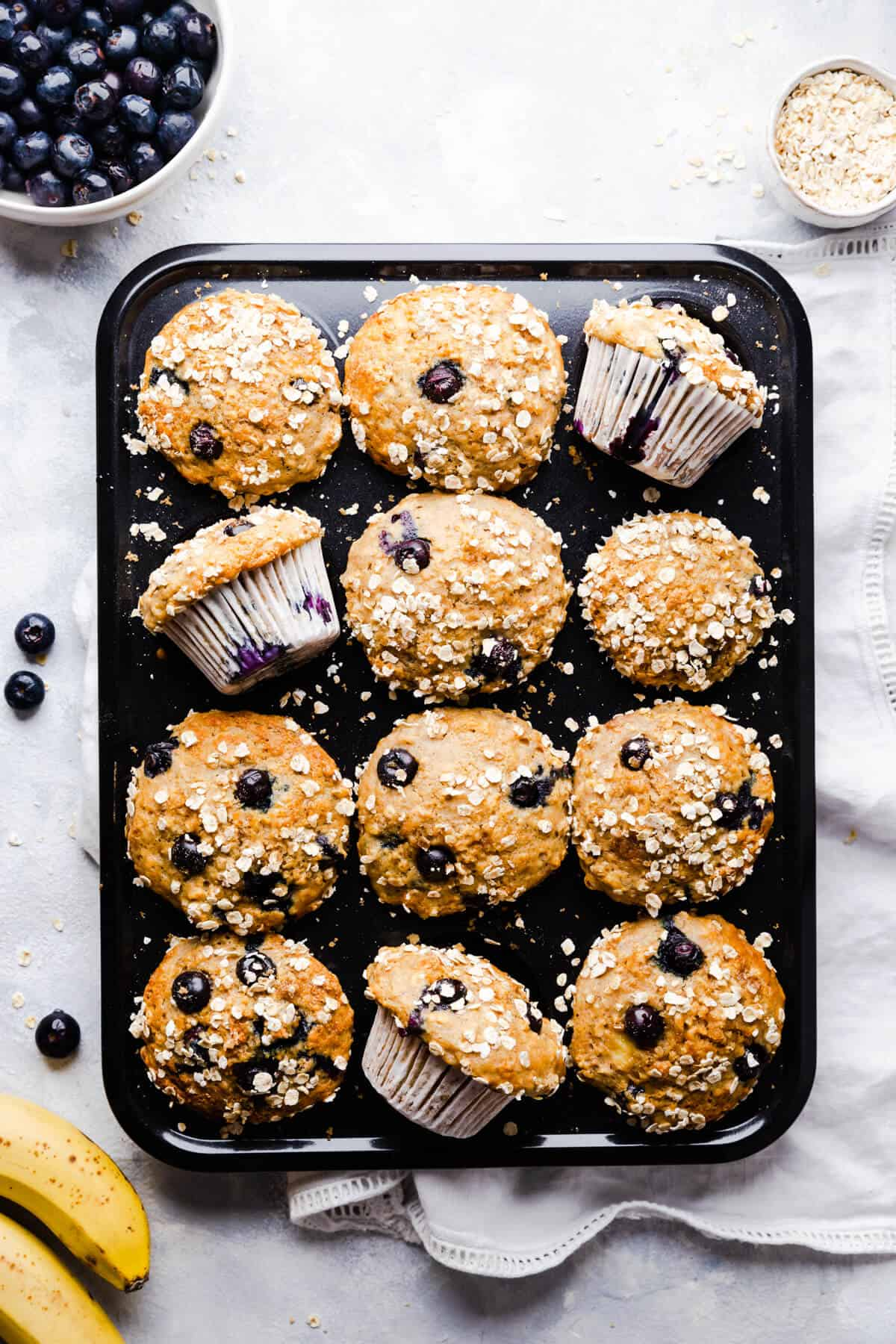 top view of a muffin tin filled with banana and blueberry muffins