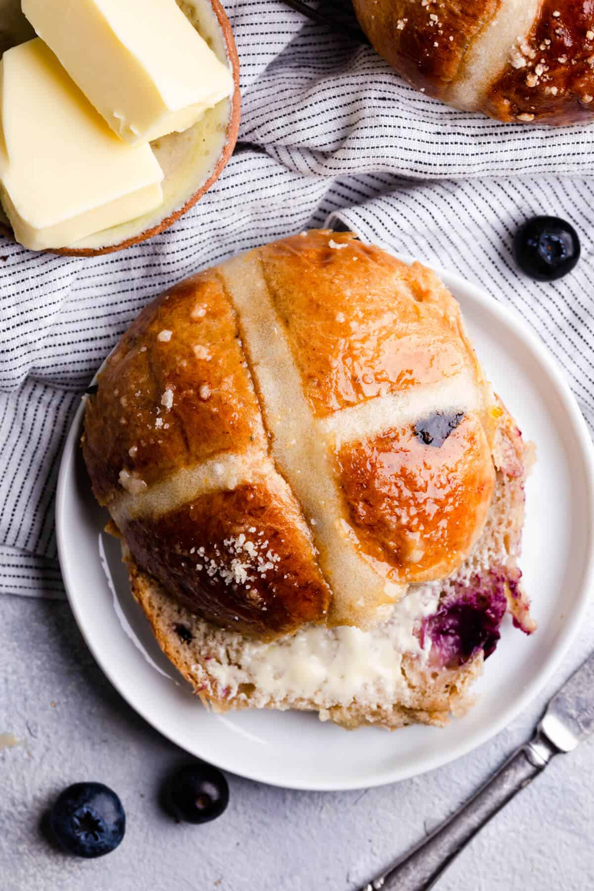top view close up photo of blueberry hot cross bun with butter