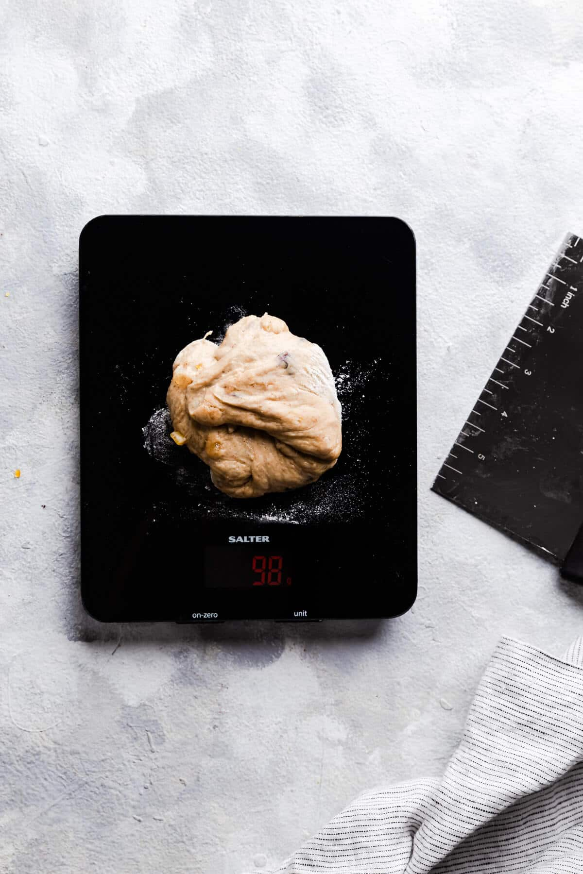 top view of digital kitchen scales with piece of dough on top