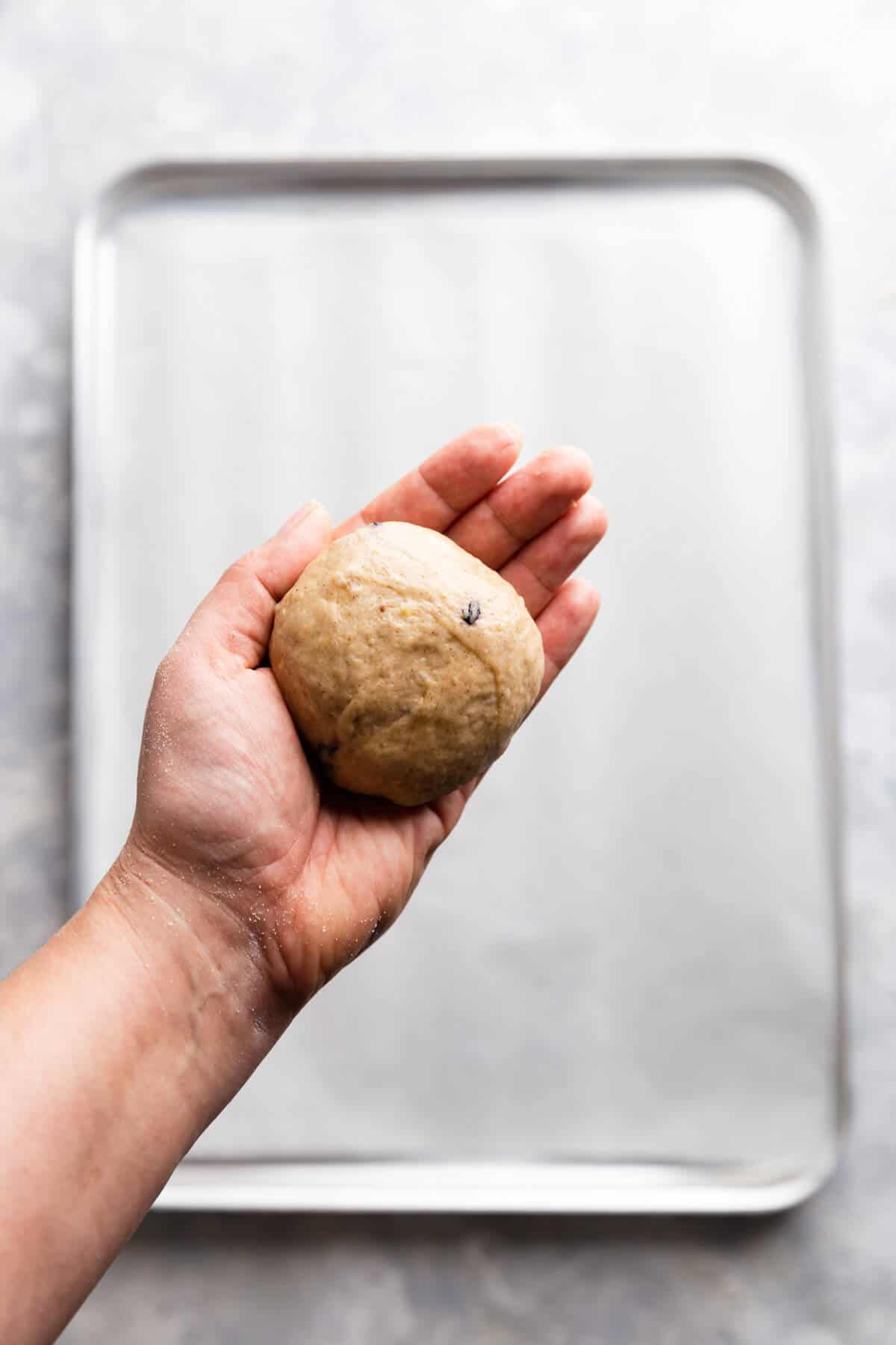 a close up at a hand holding a ball of dough