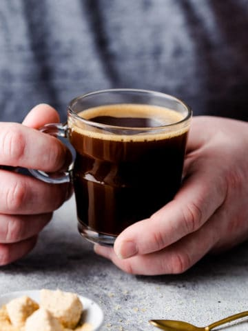 side close up of a person holding a small cup of coffee
