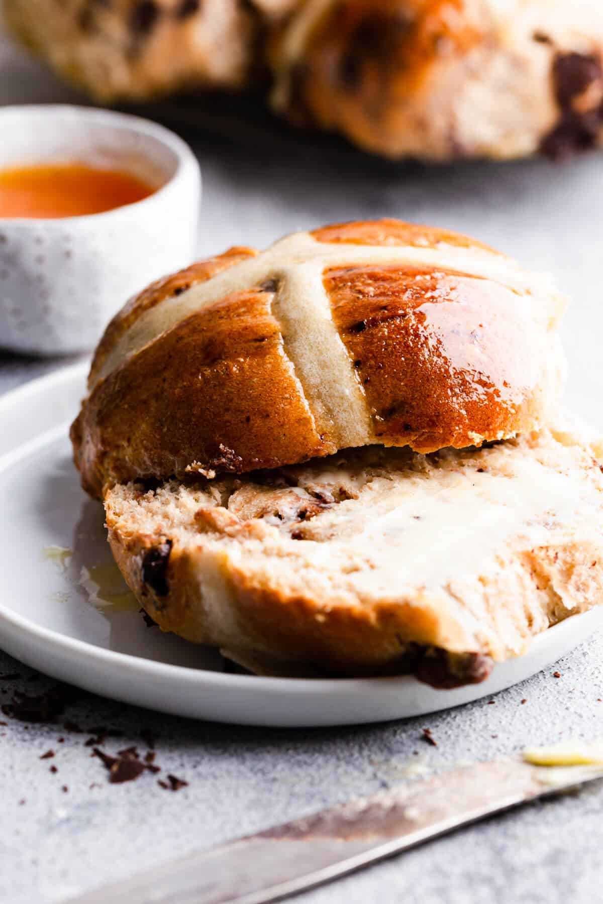 side close up at a hot cross bun with butter
