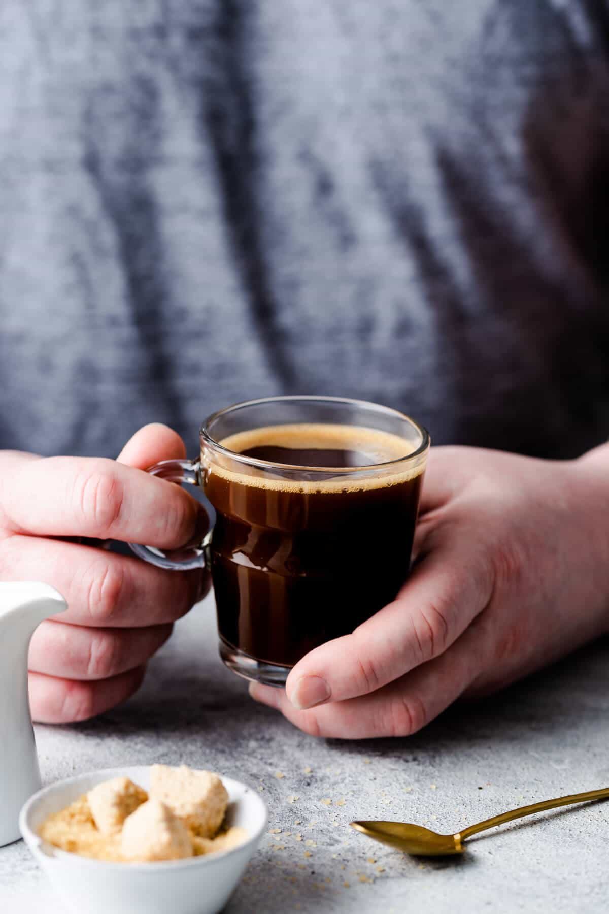 side close up of a person holding a cup of coffee