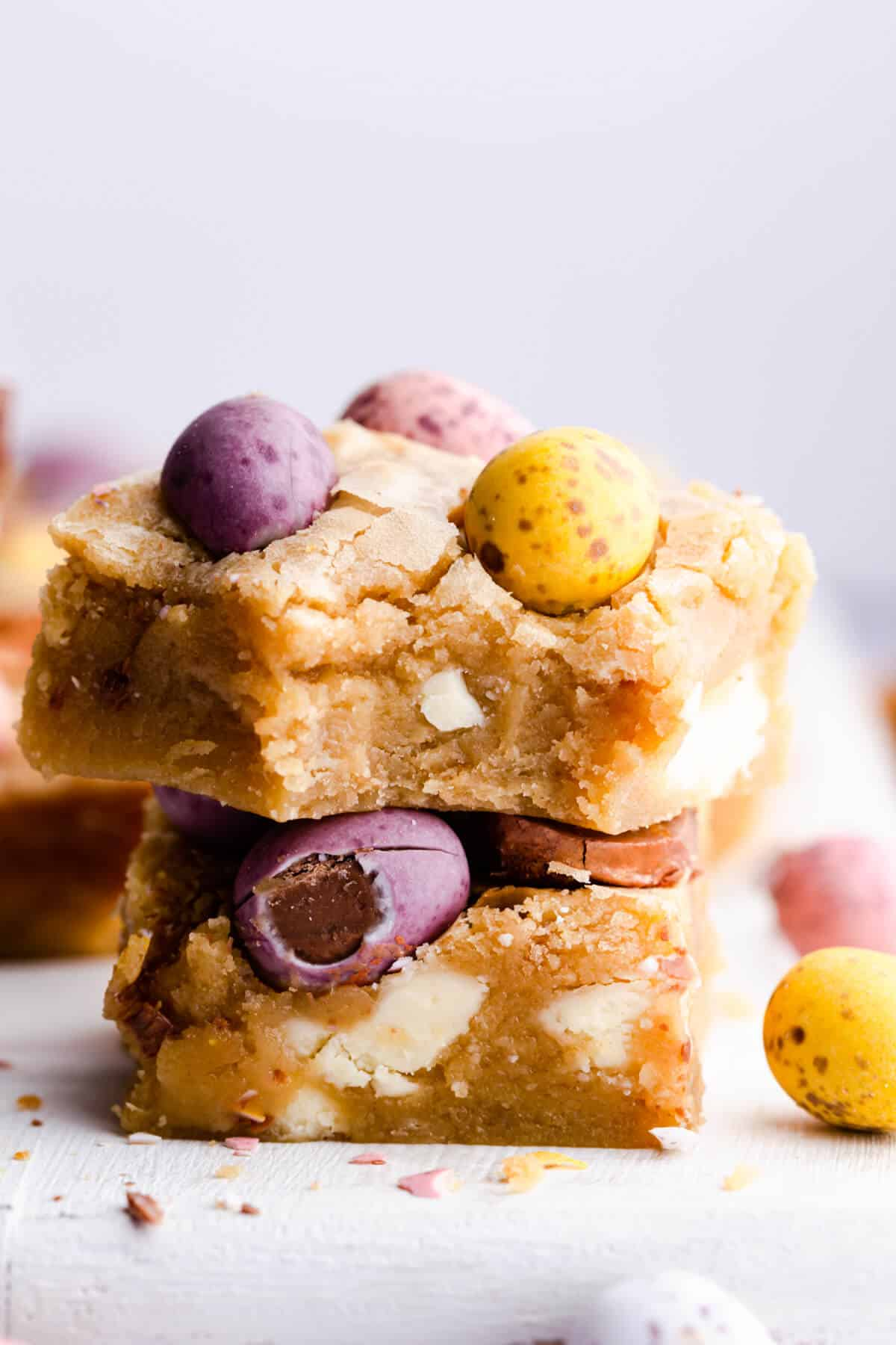 side super close up of two square slices of blondies with mini eggs