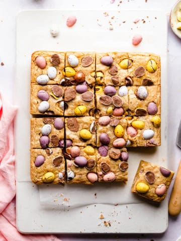 top view photo of blondie cake cut into square slices topped with mini eggs