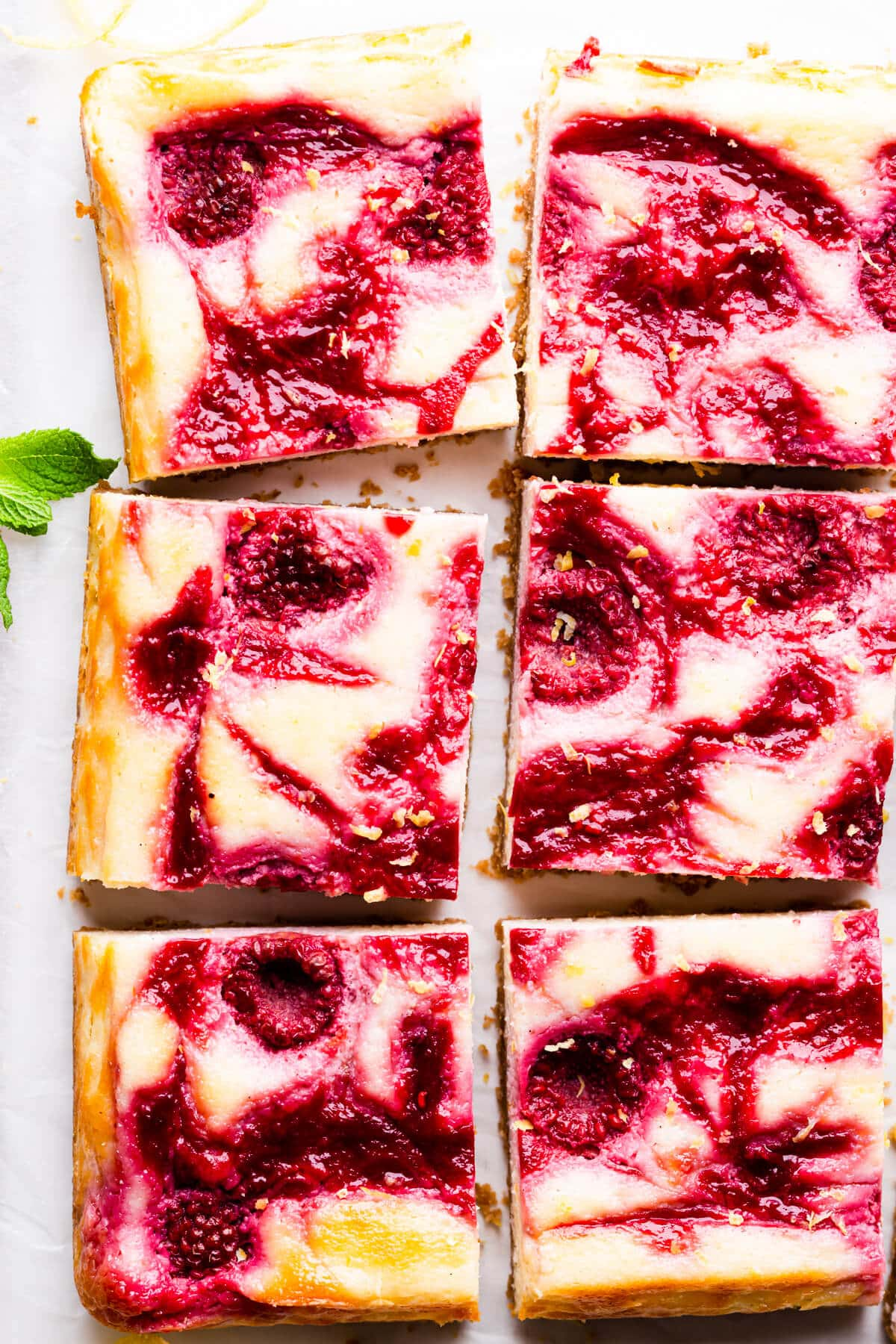 top down super close up of cheesecake bars with raspberry swirls