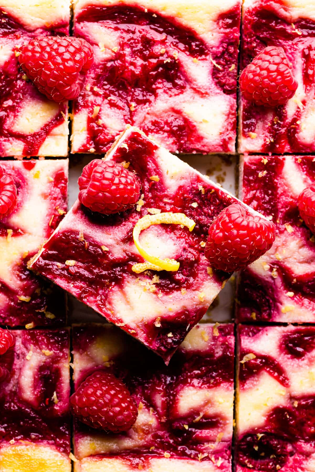top down super close up at a square slice of raspberry lemon cheesecake bar